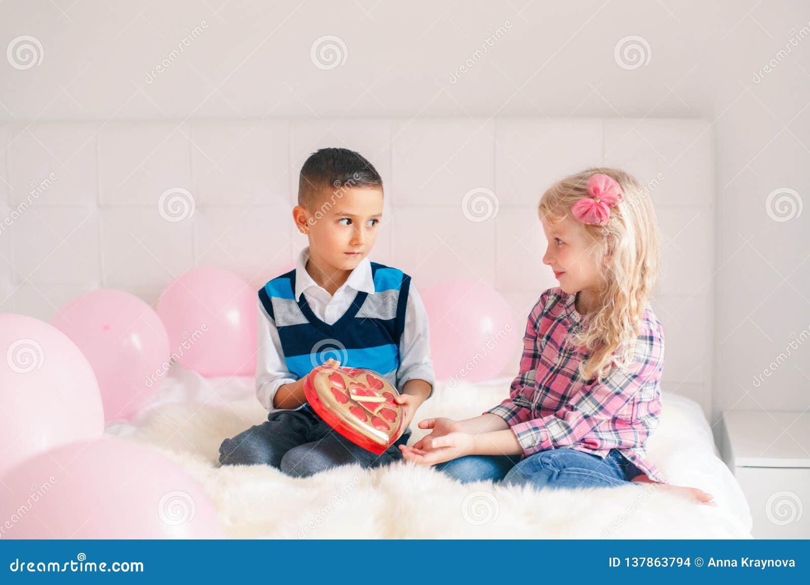 Αγόρι που δίνει το δώρο σοκολάτας κοριτσιών παρόν για να γιορτάσει την ημέρα βαλεντίνων