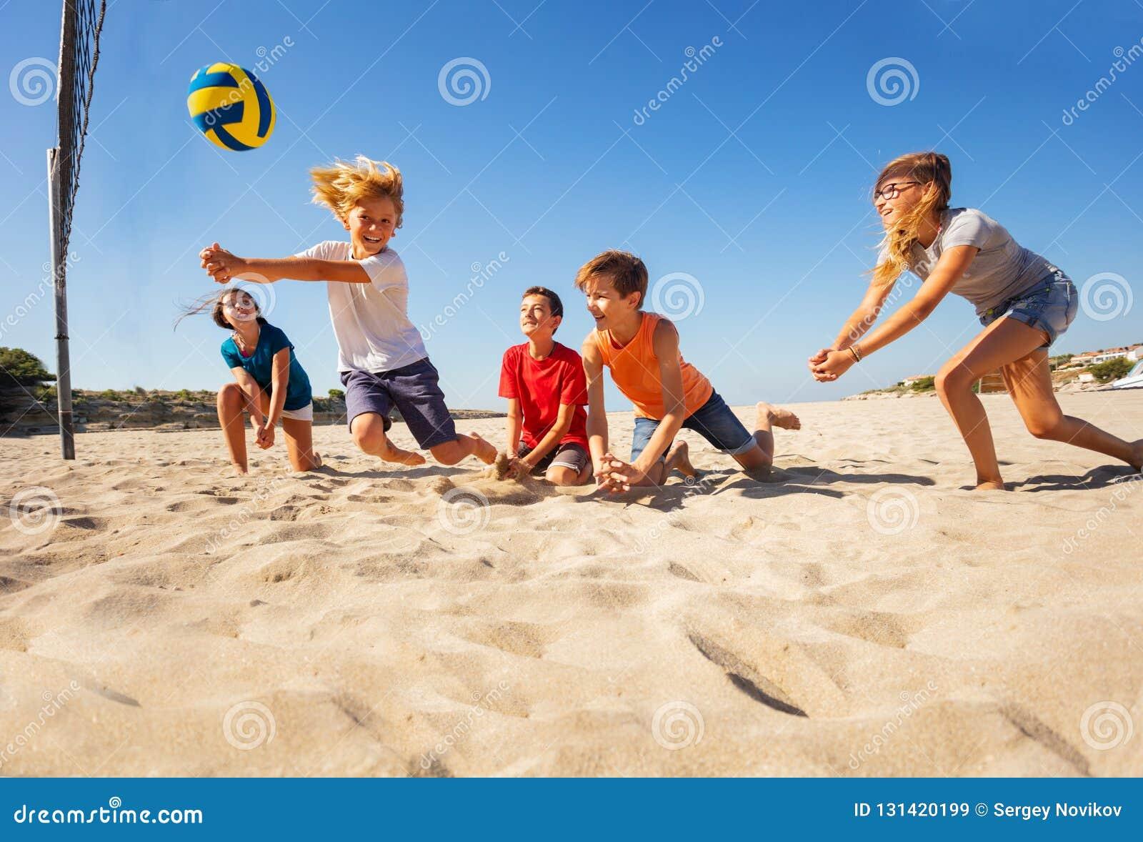 Αγόρι που κάνει την πρόσκρουση να περάσει κατά τη διάρκεια του παιχνιδιού πετοσφαίρισης παραλιών