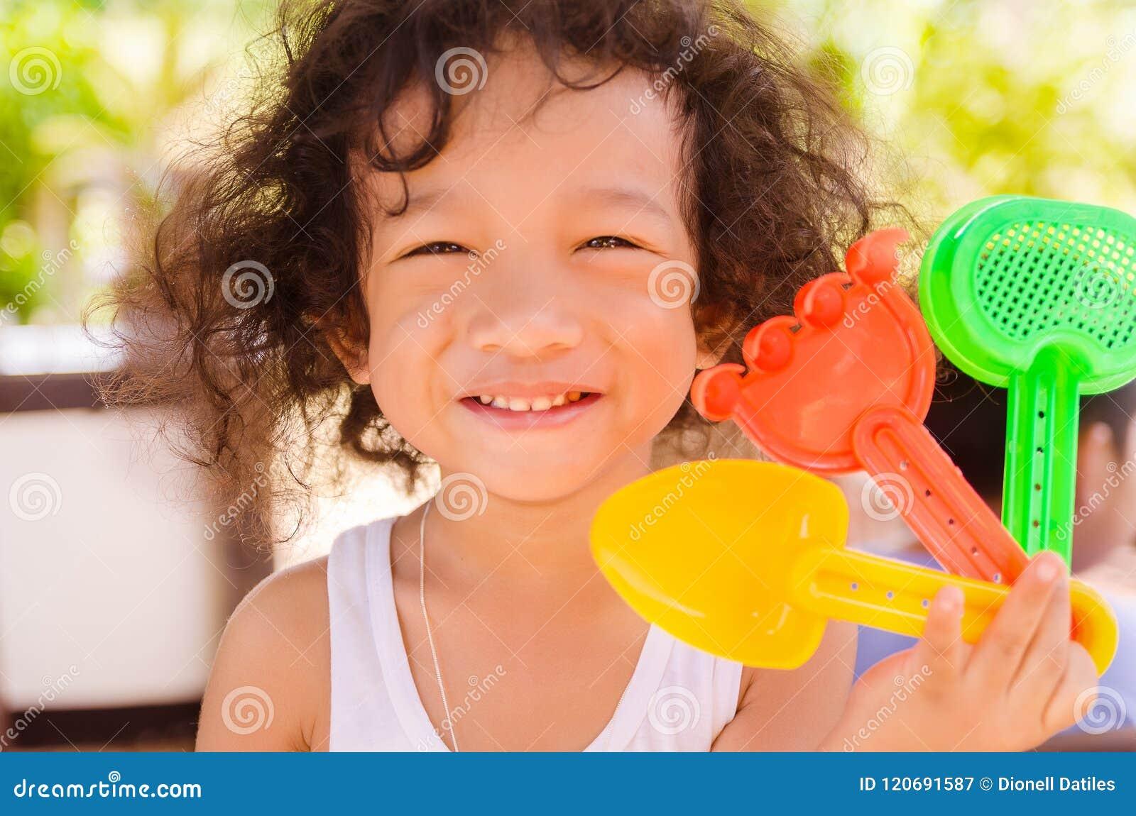 Αγόρι που κρατά τα ζωηρόχρωμα πλαστικά παιχνίδια