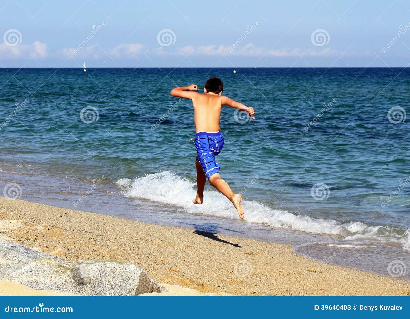 Αγόρι που τρέχει στην παραλία θάλασσας