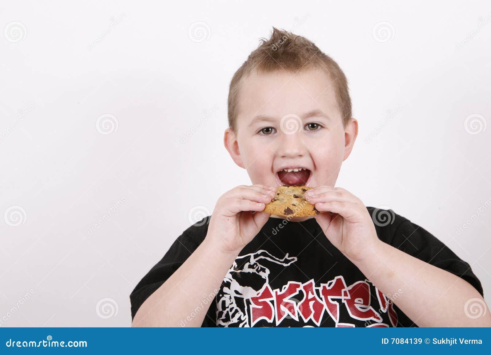 αγόρι που τρώει το γλυκό τροφίμων
