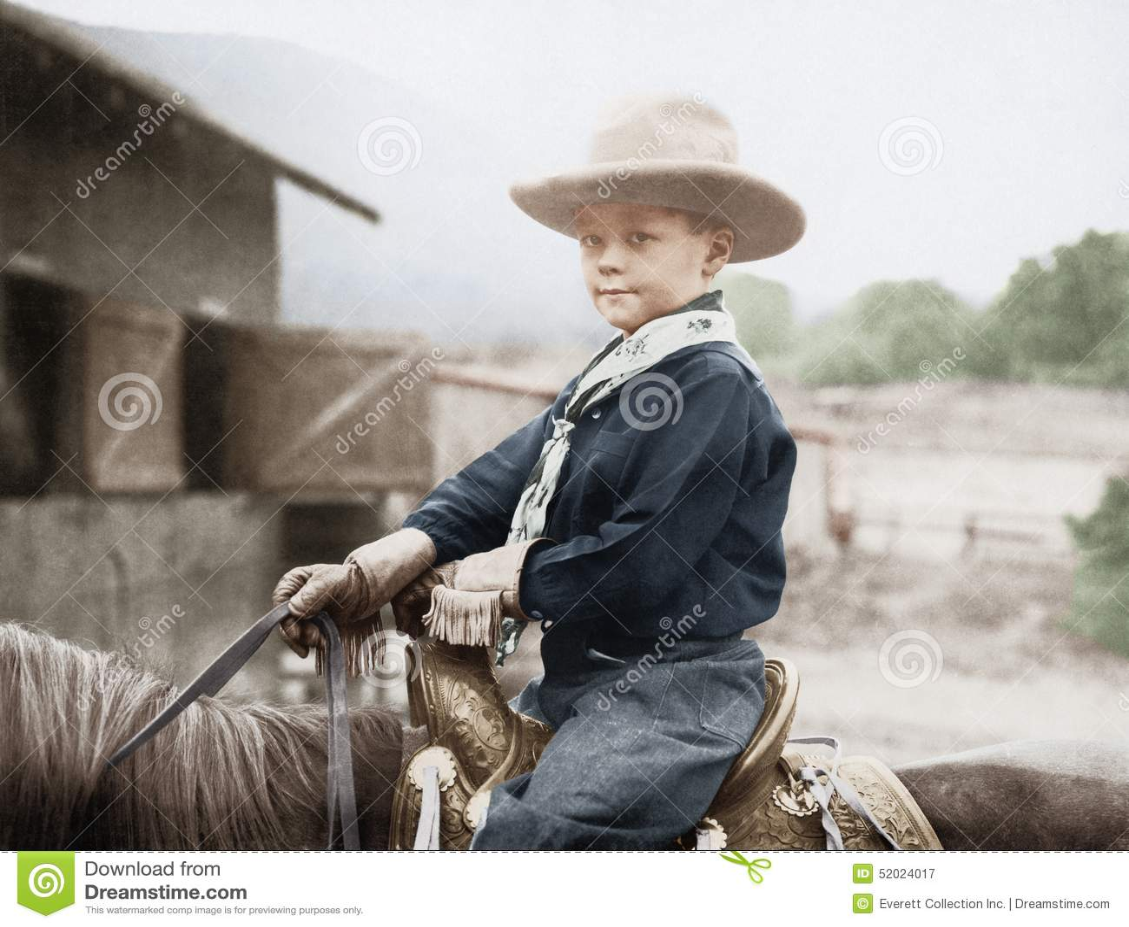 Αγόρι σε ένα καπέλο κάουμποϋ σε ένα άλογο (όλα τα πρόσωπα που απεικονίζονται δεν ζουν περισσότερο και κανένα κτήμα δεν υπάρχει Εξ