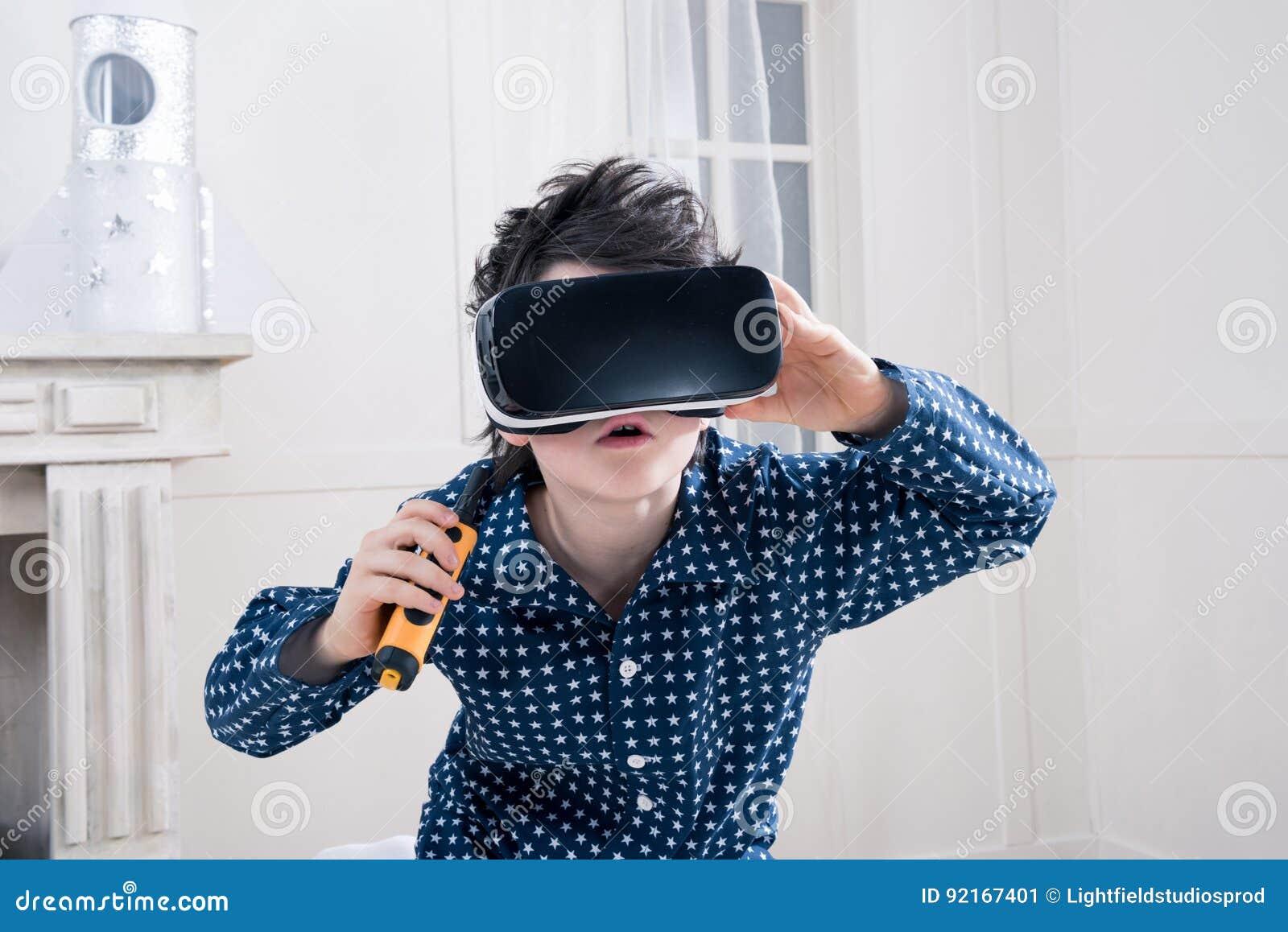 Αγόρι στις πυτζάμες που φορούν την κάσκα εικονικής πραγματικότητας και που κρατούν walkie-talkie