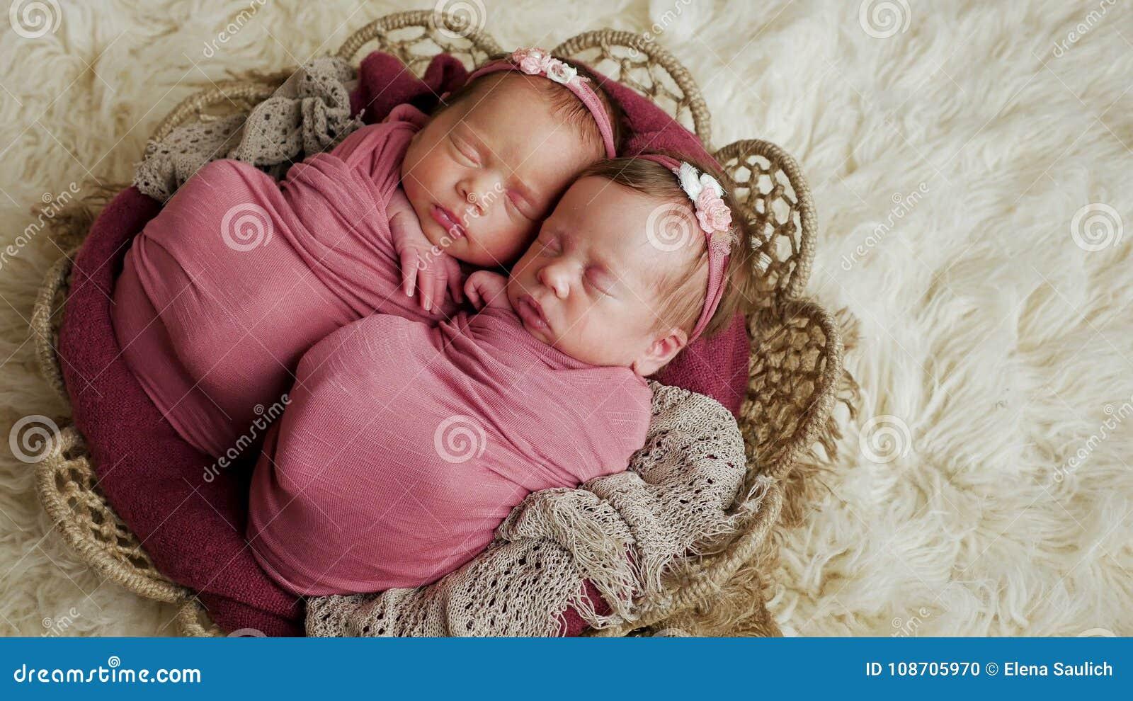 Αδελφές διδύμων νεογέννητες στο τύλιγμα και σε ένα καλάθι