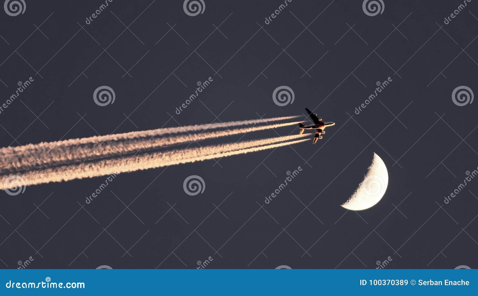 Αεροπλάνο εμιράτων που περνά το φεγγάρι στον ουρανό