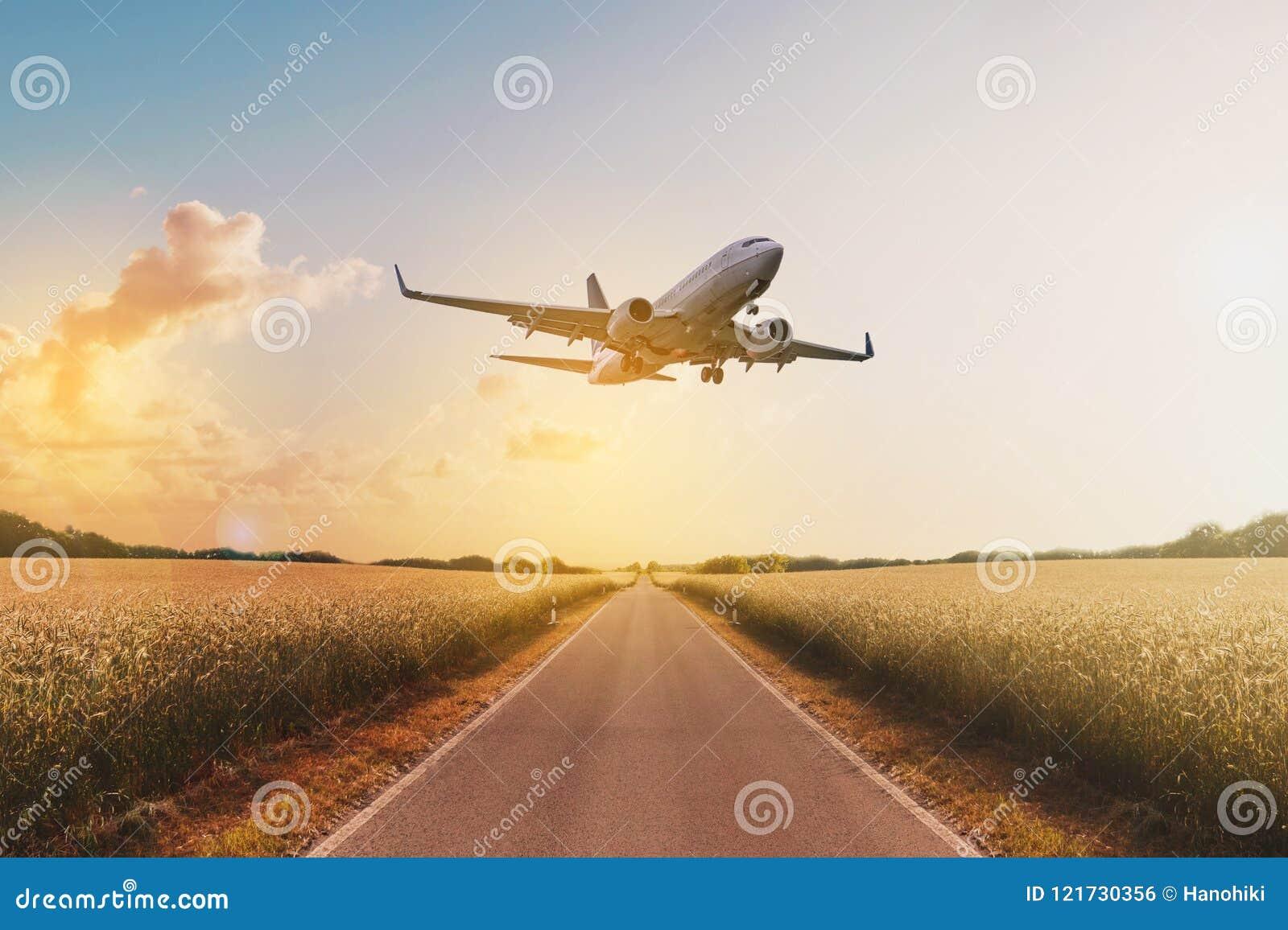 Αεροπλάνο που πετά επάνω από τον κενό δρόμο στο αγροτικό τοπίο - ταξίδι ομο
