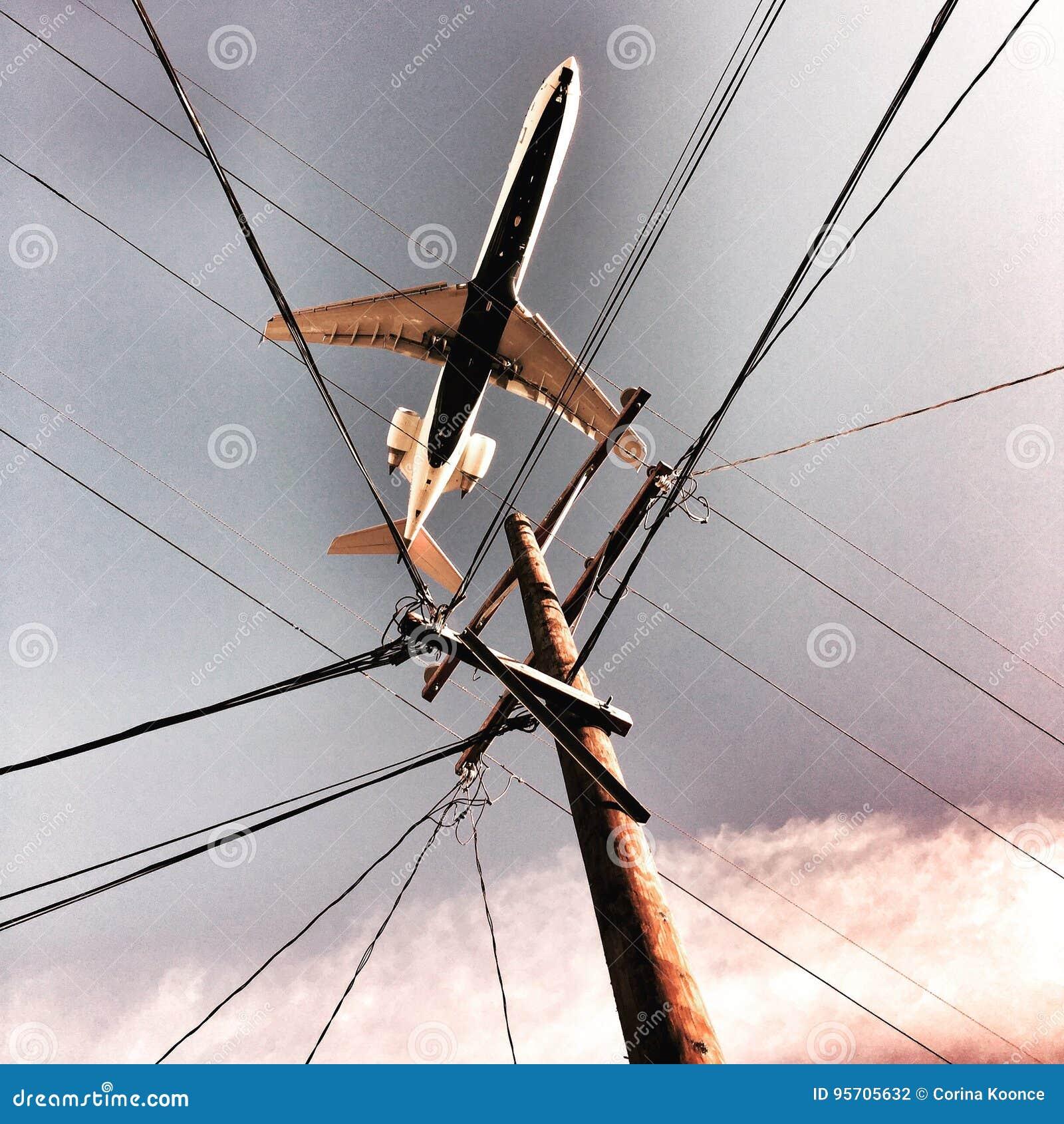 Αεροπλάνο επάνω από τα ηλεκτροφόρα καλώδια