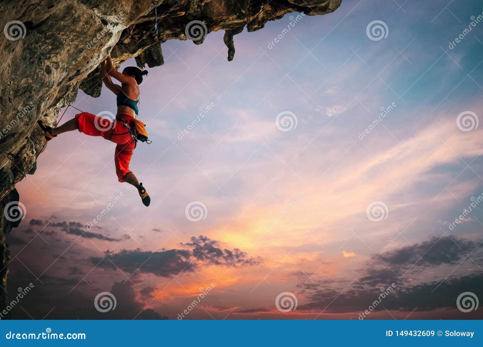 Αθλητική γυναίκα που αναρριχείται στο overhanging βράχο απότομων βράχων με το υπόβαθρο ουρανού ηλιοβασιλέματος