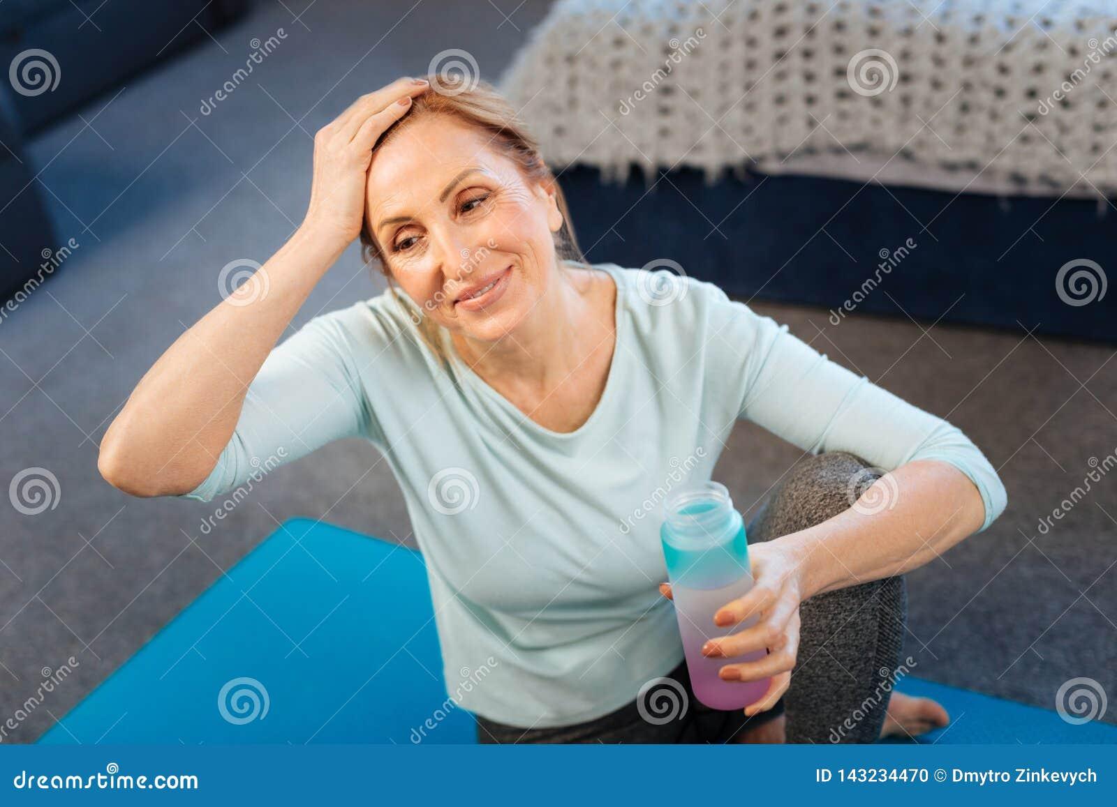 Αθλητική κατάλληλη κυρία που κουράζεται και τρίβοντας το μέτωπό της