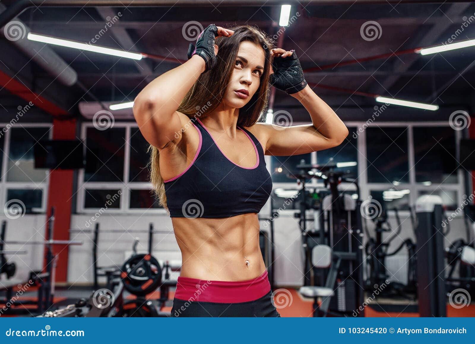 Αθλητική νέα γυναίκα που παρουσιάζει μυς μετά από το workout στη γυμναστική