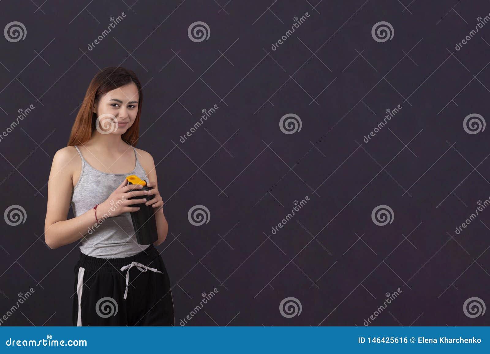 Αθλητικό κορίτσι μετά από τα αθλητικά ποτά παιχνιδιού από έναν δονητή με ένα υγρό πουκάμισο από τον ιδρώτα copyspace