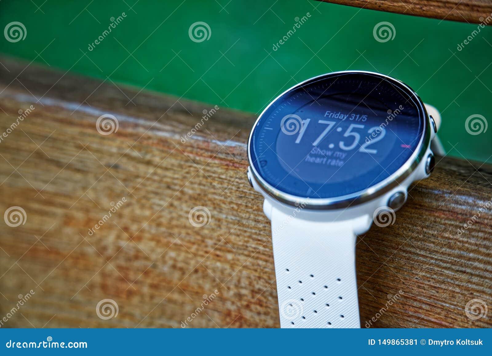 Αθλητικό ρολόι για το τρέξιμο του άσπρου χρώματος στον ξύλινο πάγκο Ρολόι ικανότητας για την καταδίωξη της καθημερινής κατάρτισης