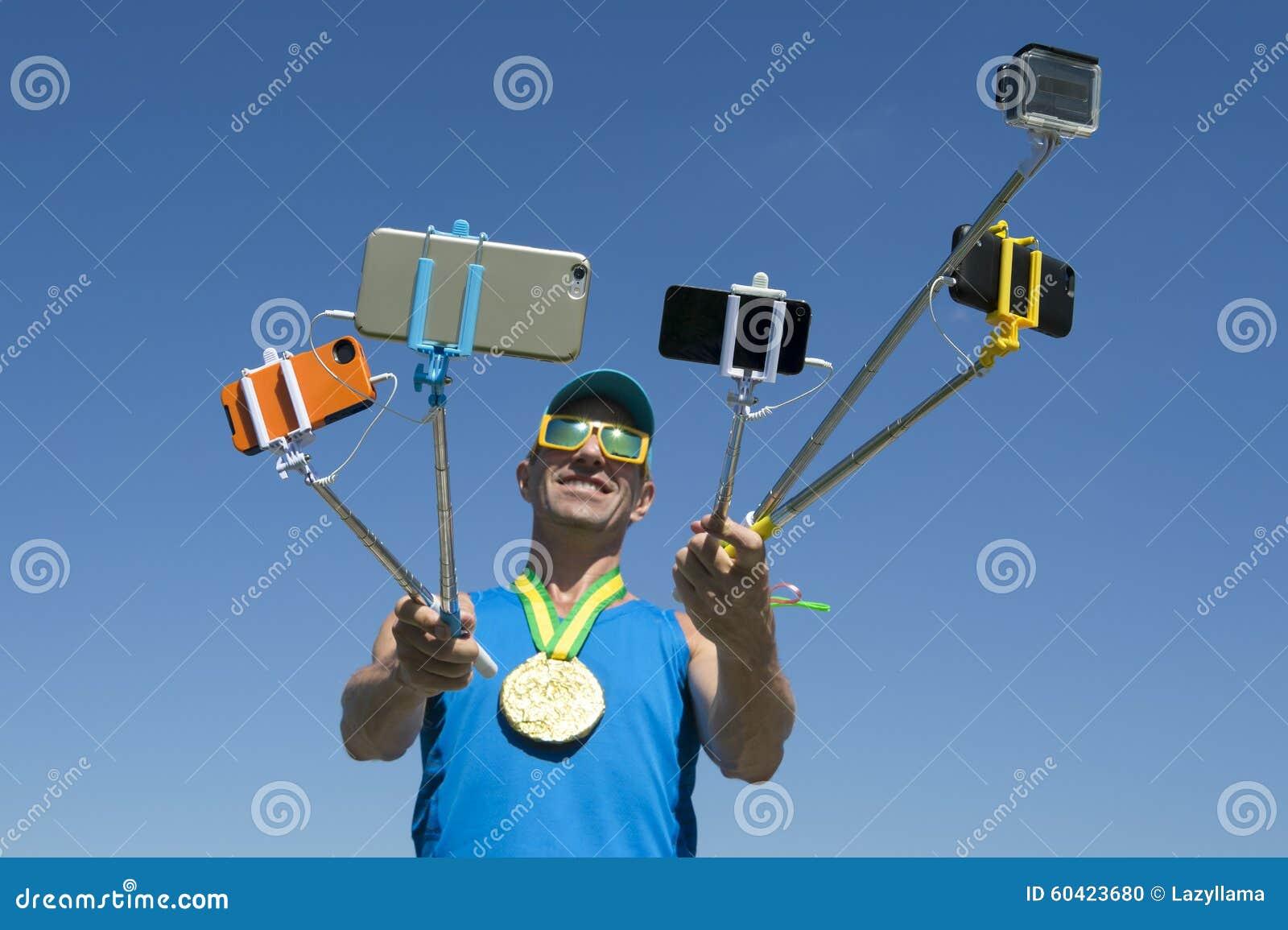 Αθλητής χρυσών μεταλλίων που παίρνει Selfies με τα ραβδιά Selfie