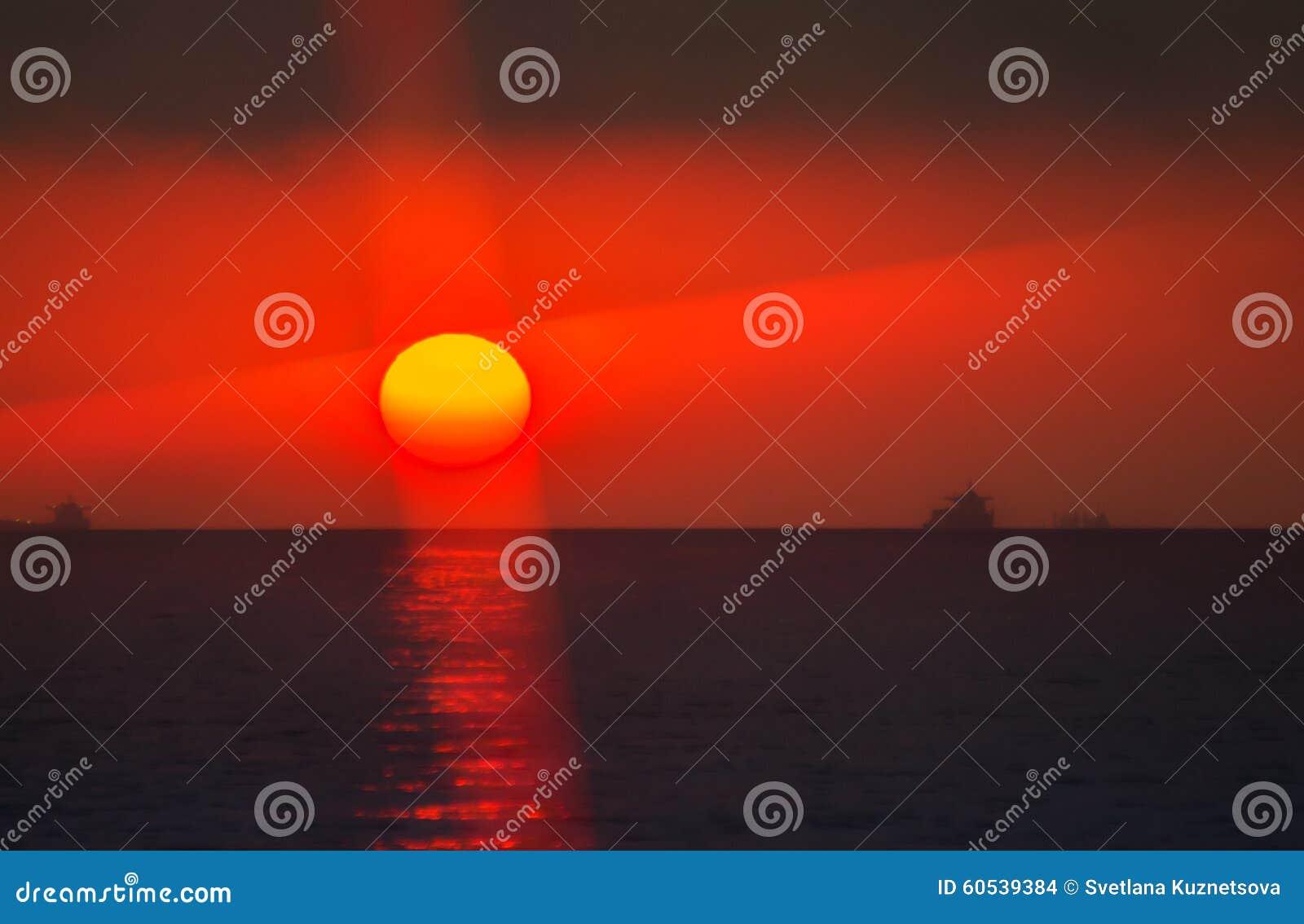 Αιματηρός ήλιος μεταξύ της θάλασσας και του σύννεφου