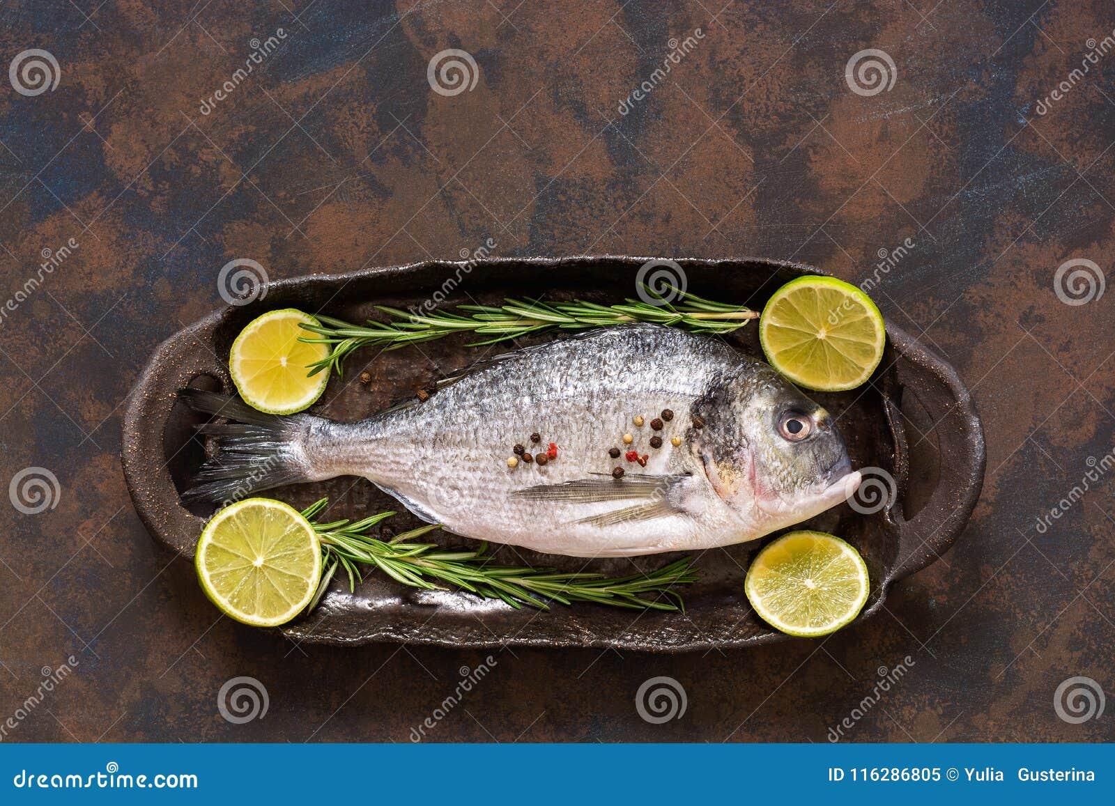 Ακατέργαστα φρέσκα ψάρια με τις φέτες και το δεντρολίβανο ασβέστη Μια τοπ άποψη, μια θέση για το κείμενό σας ή διαφήμιση