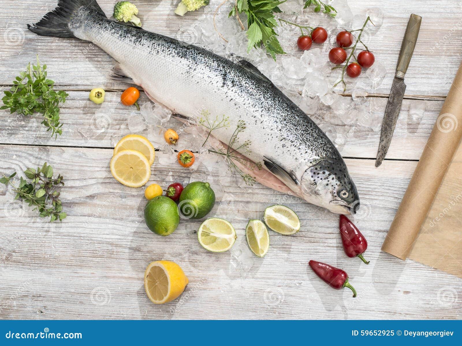 Ακατέργαστα ψάρια σολομών στον πάγο και τα λαχανικά