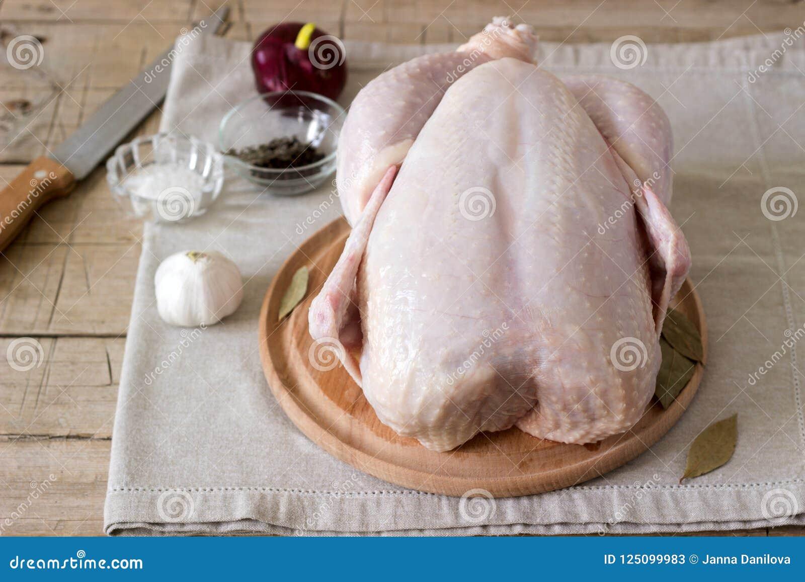 Ακατέργαστο κοτόπουλο σε έναν ξύλινο πίνακα με τα καρυκεύματα και τα λαχανικά