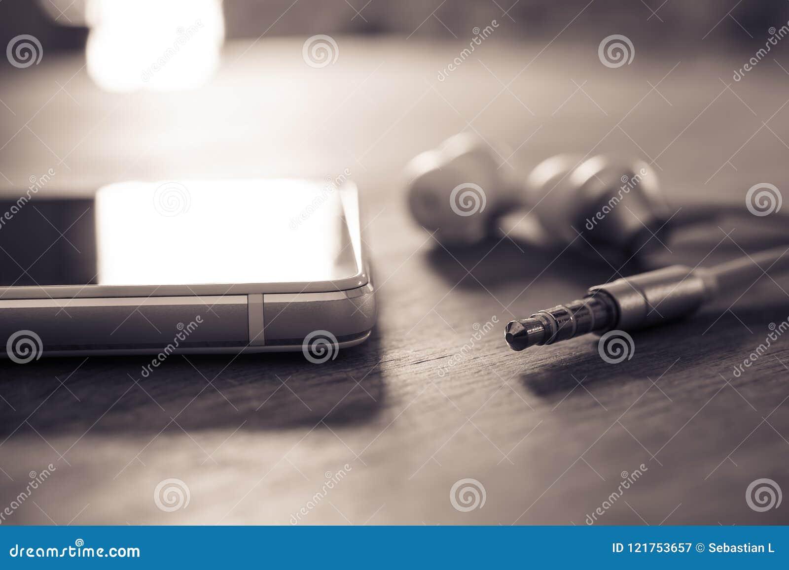 Ακουστικά και καλώδιο -αυτιών που βρίσκονται δίπλα σε ένα άσπρο κινητό τηλέφωνο στα μονοχρωματικά χρώματα