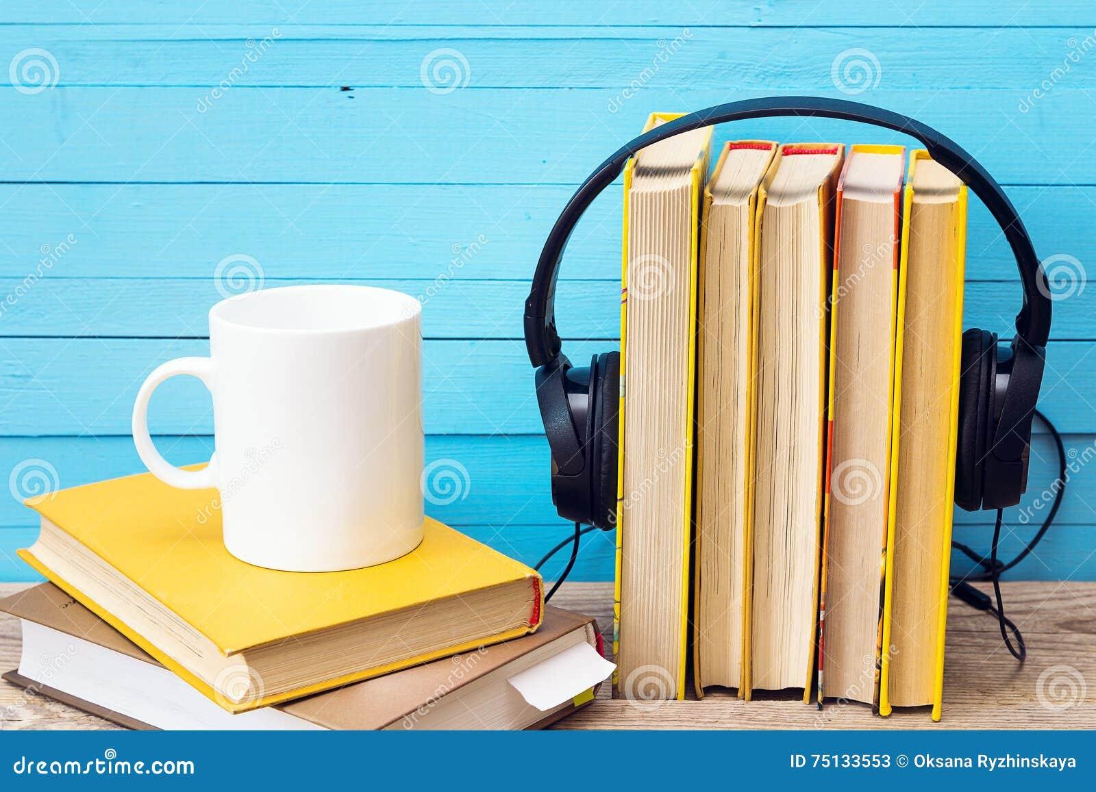 Ακουστική έννοια βιβλίων, βιβλίο και ακουστικά και κούπα καφέ πέρα από το ξύλο