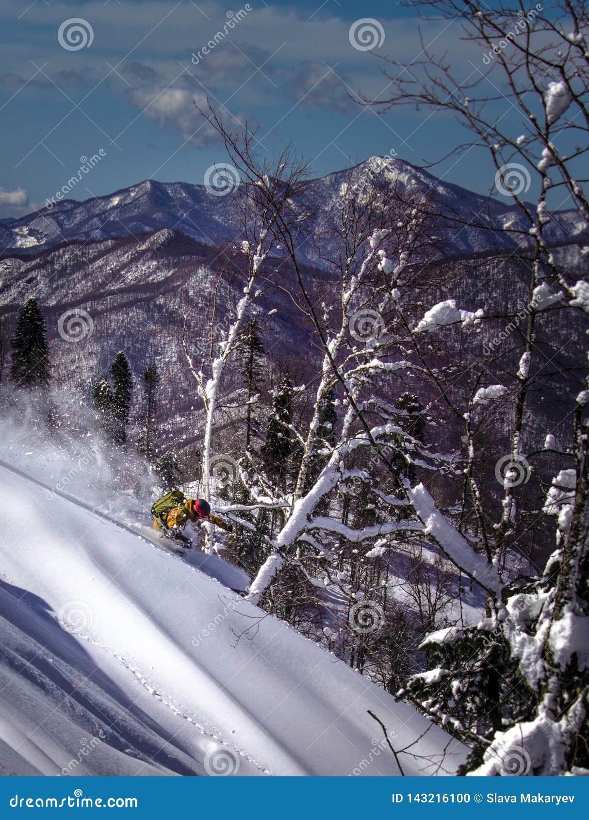 Ακραίο χιόνι συντριβής σκιέρ που έρχεται κάτω από το βουνό