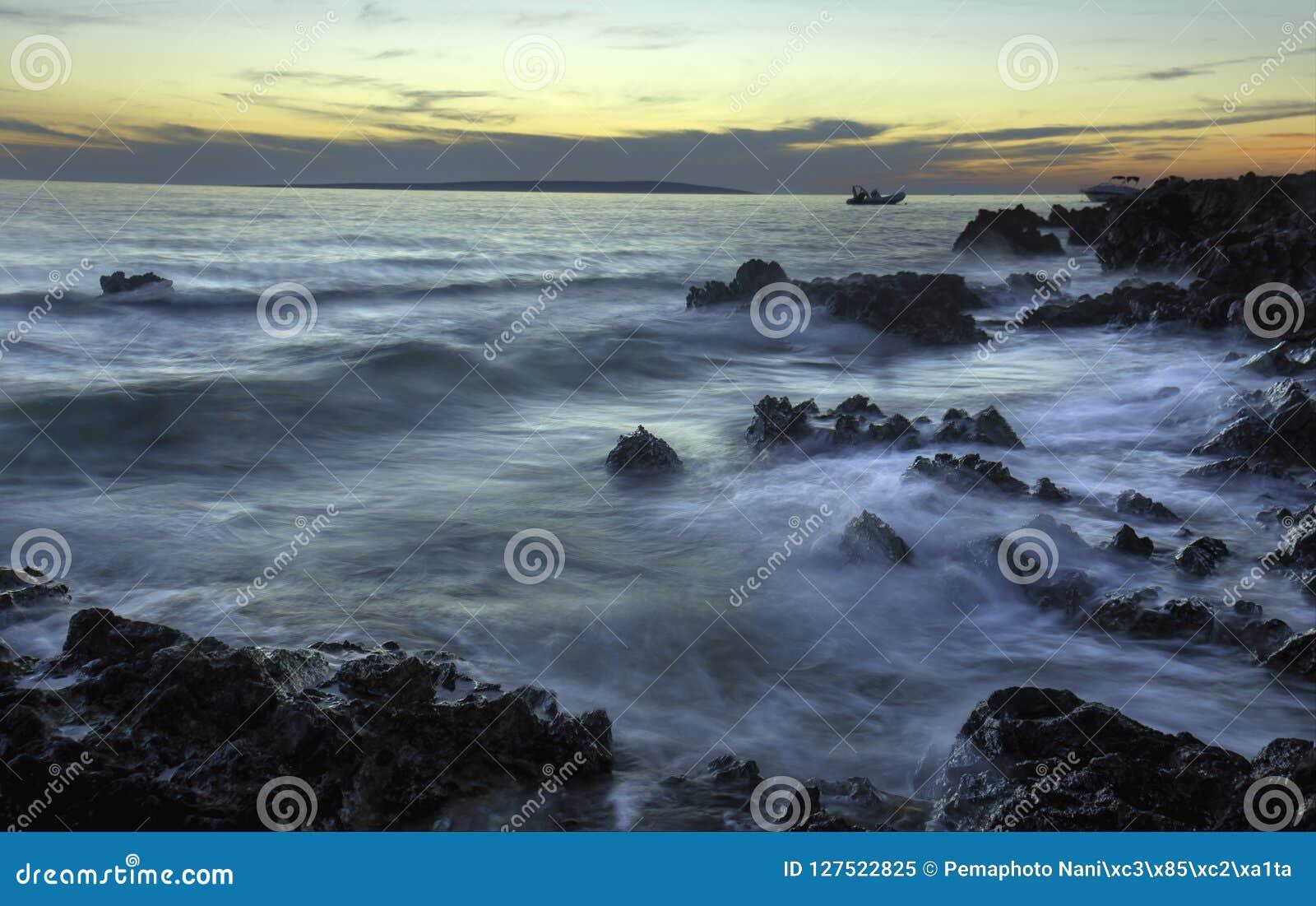 Ακτή ηλιοβασιλέματος με τους βράχους και την επίγεια βιασύνη