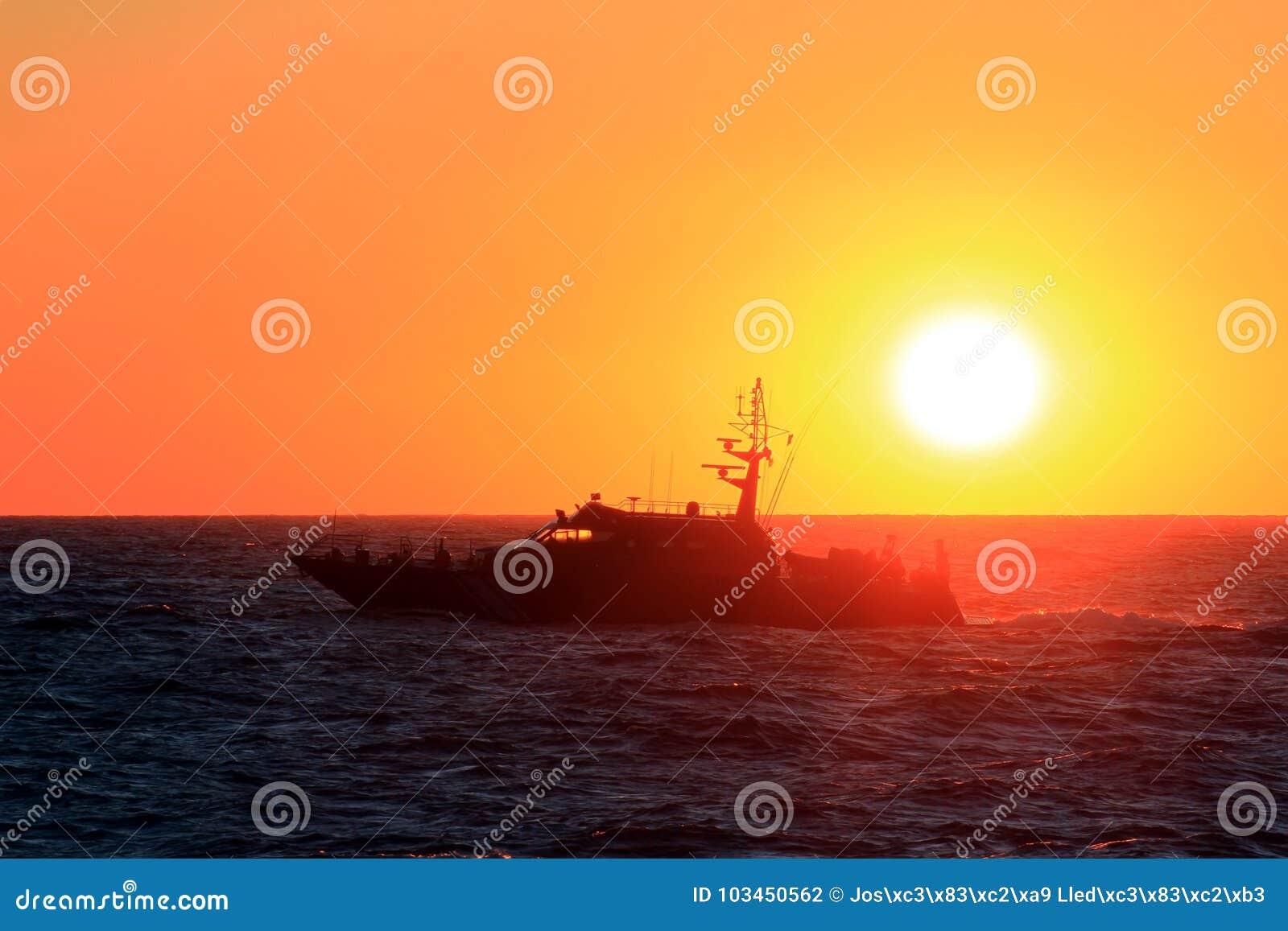 Ακτοφυλακή που πλέει κατά τη διάρκεια του ηλιοβασιλέματος