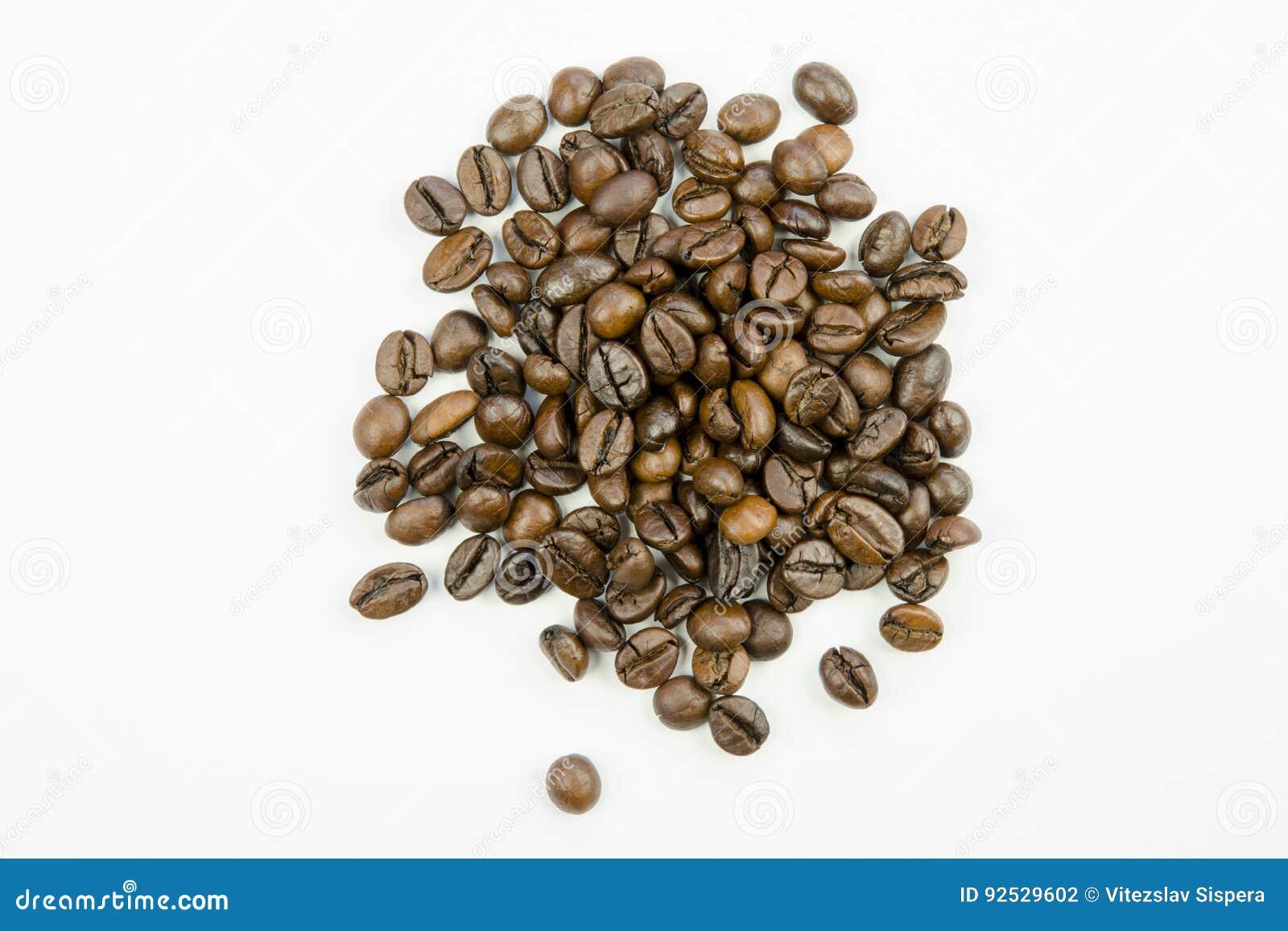 Ακόμα ζωή με την άποψη κινηματογραφήσεων σε πρώτο πλάνο των σιταριών του ψημένου καφετιού καφέ που απομονώνεται