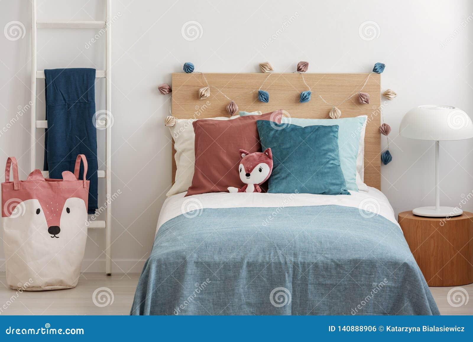 Αλεπού βελούδου στο κρεβάτι καψαλισμάτων με τα ζωηρόχρωμα μαξιλάρια και duvet