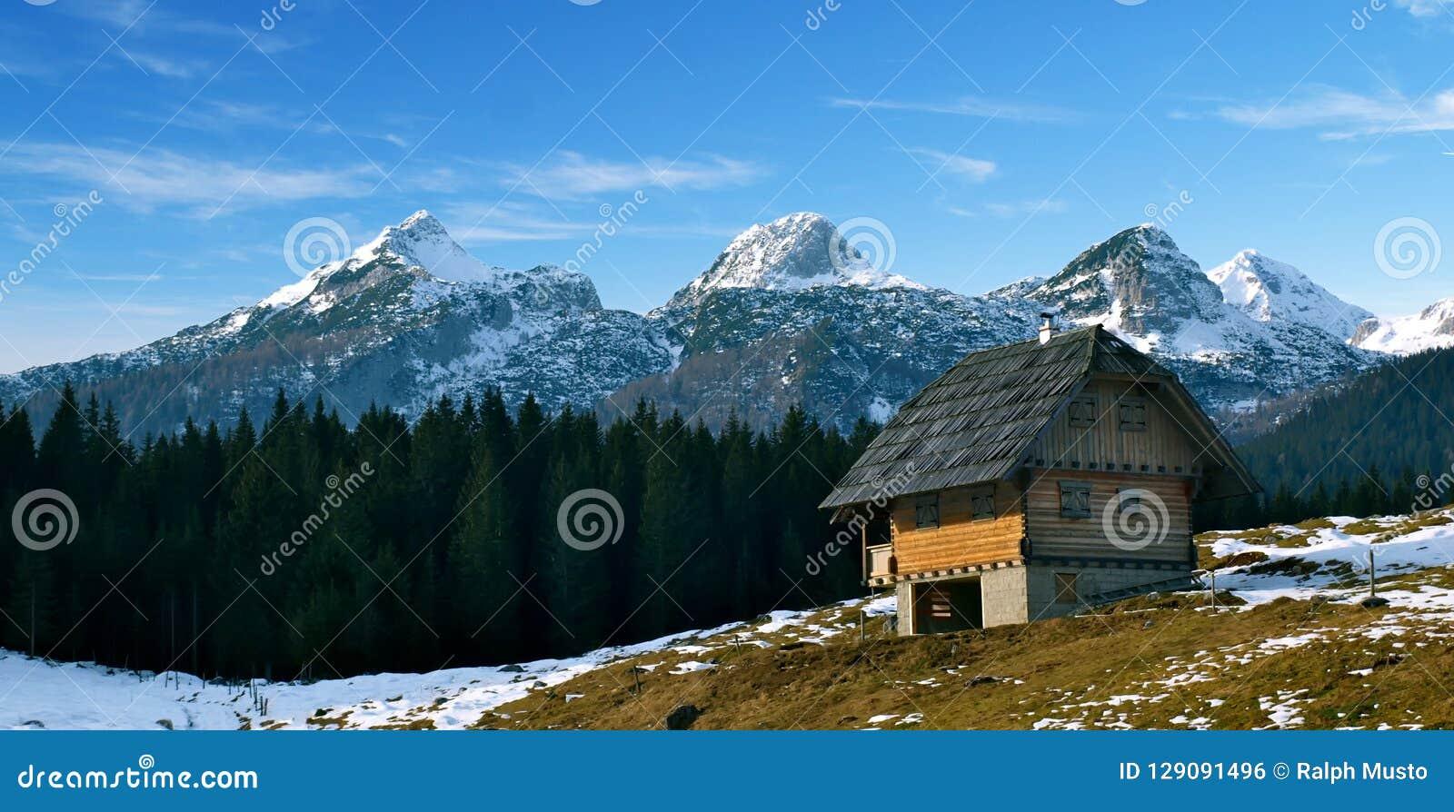 Αλπική καλύβα βουνών με τις χιονώδεις αιχμές