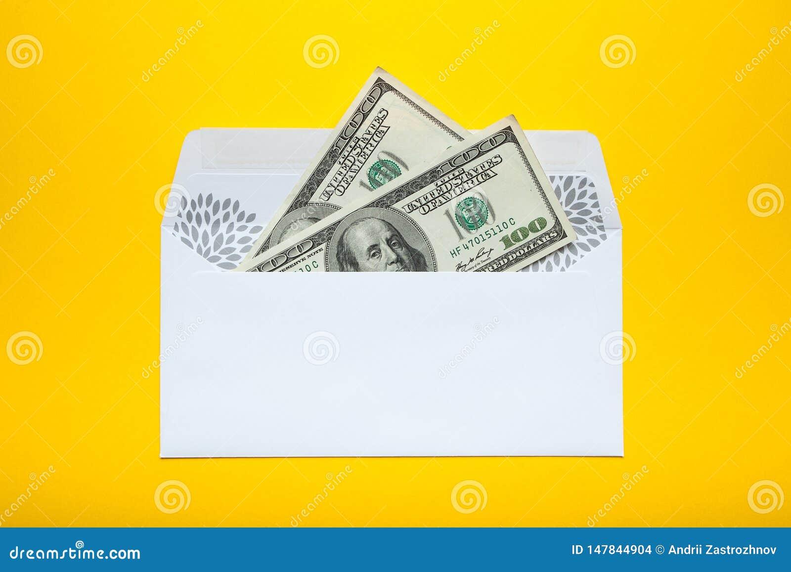 Αμερικανικά δολάρια στον άσπρο φάκελο που απομονώνεται στο κίτρινο υπόβαθρο