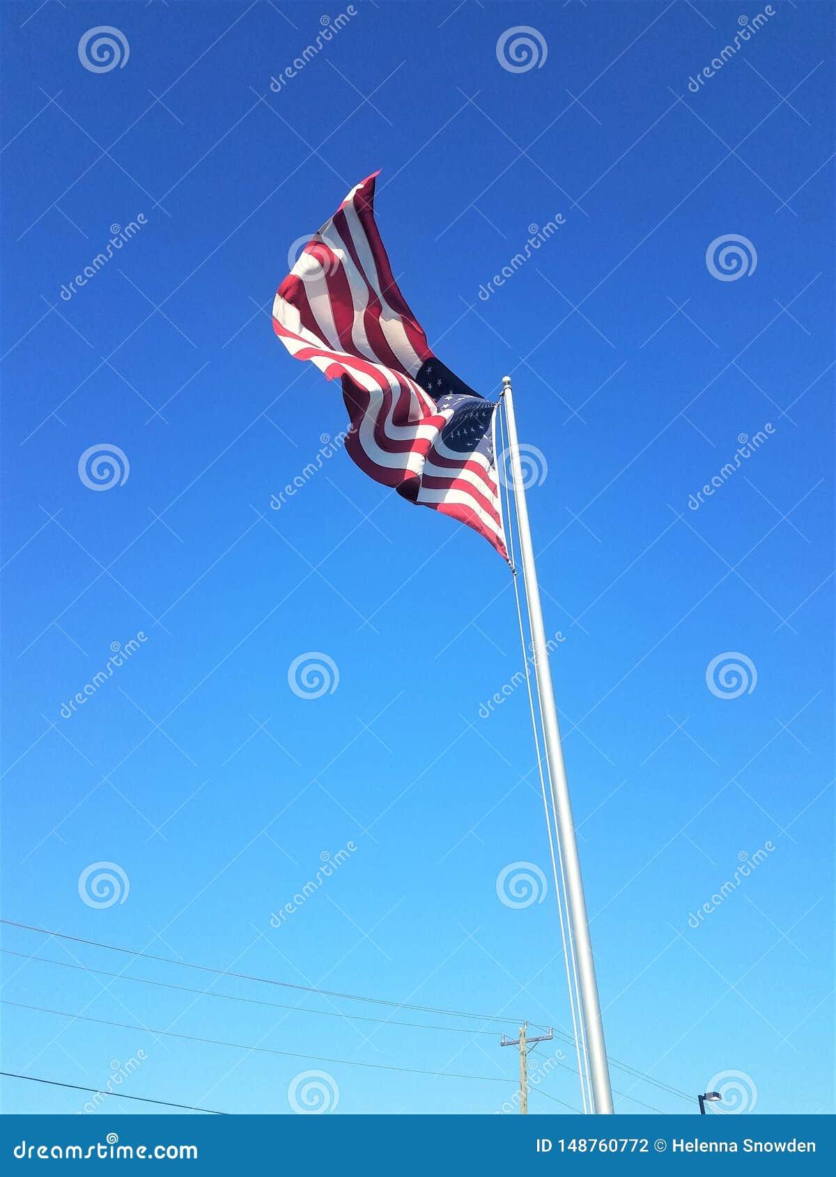 Αμερικανική σημαία που κυματίζει στον αέρα μπροστά από έναν μπλε ουρανό
