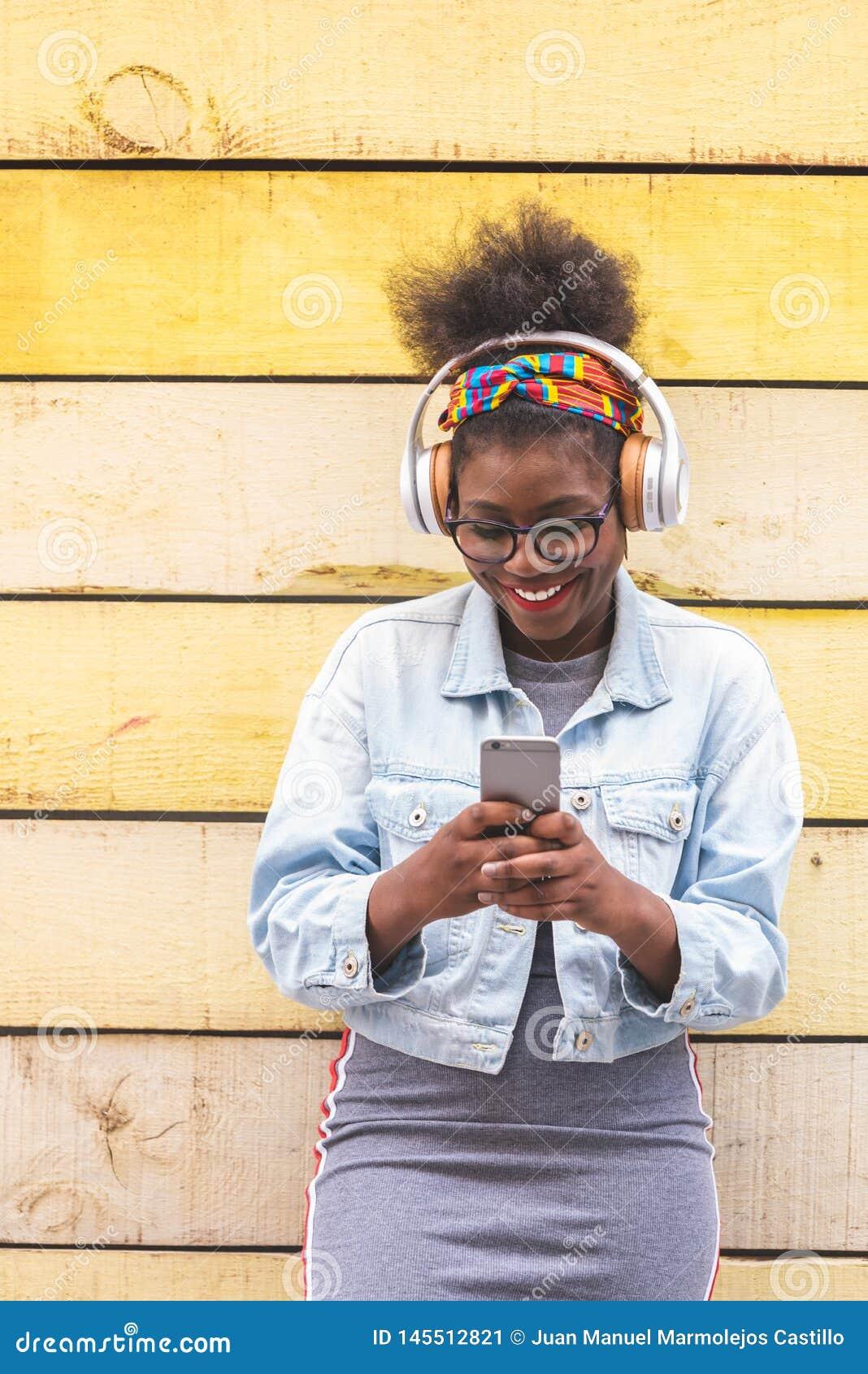 Αμερικανικό έφηβη Afro που χρησιμοποιεί το κινητό τηλέφωνο υπαίθρια