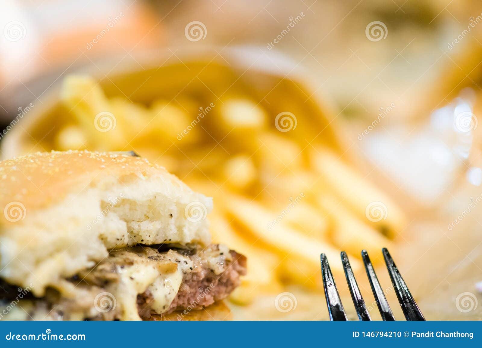 αμερικανικό χάμπουργκερ βόειου κρέατος με το τυρί και τηγανιτές πατάτες στο όμορφο bistro γρήγορου φαγητού και καφέδων εύγευστο χ