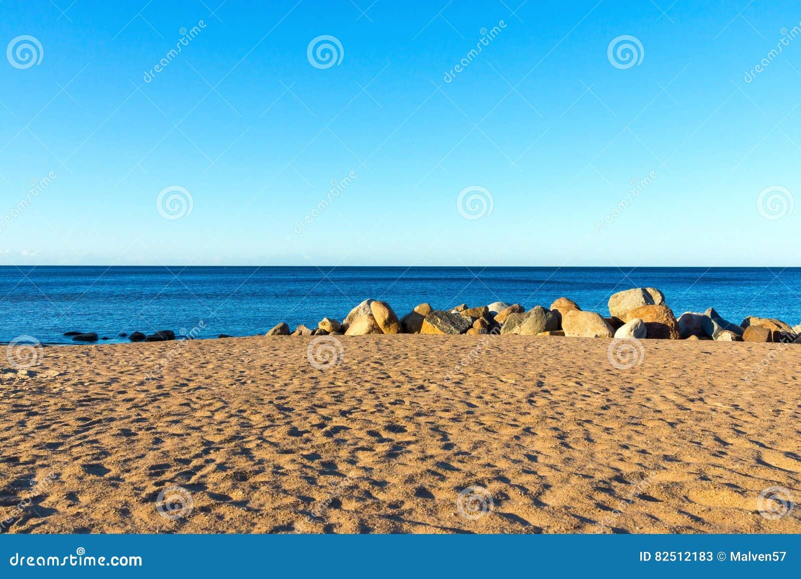 7fb7793417 Αμμώδης παραλία και μεγάλες πέτρες στην ξηρά κοντά στο νερό. Download  preview