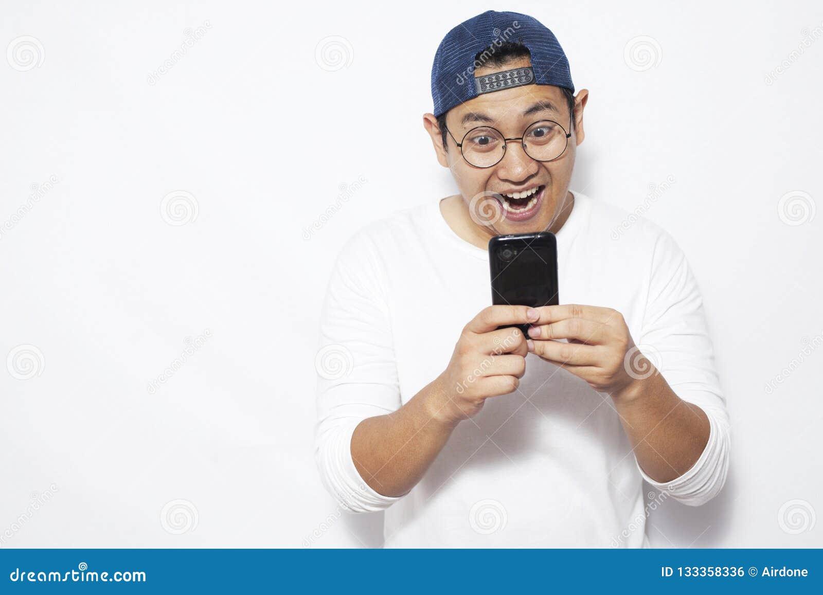 Ανάγνωση Texting νεαρών άνδρων που κουβεντιάζει στο τηλέφωνό του, χαμόγελο ευτυχές