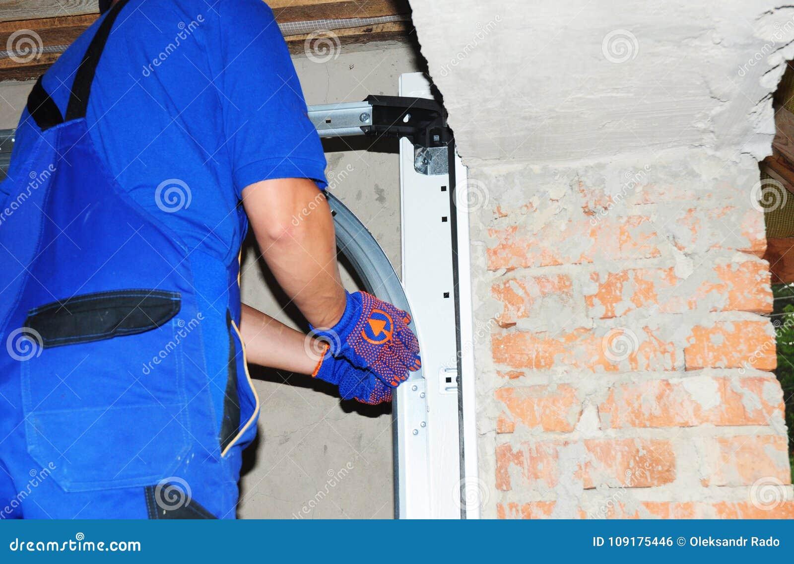 Ανάδοχος που εγκαθιστά την πόρτα γκαράζ με τη μέτρηση της ταινίας Εγκαταστήστε το σύστημα ελατηρίων ανοιχτηριών πορτών γκαράζ