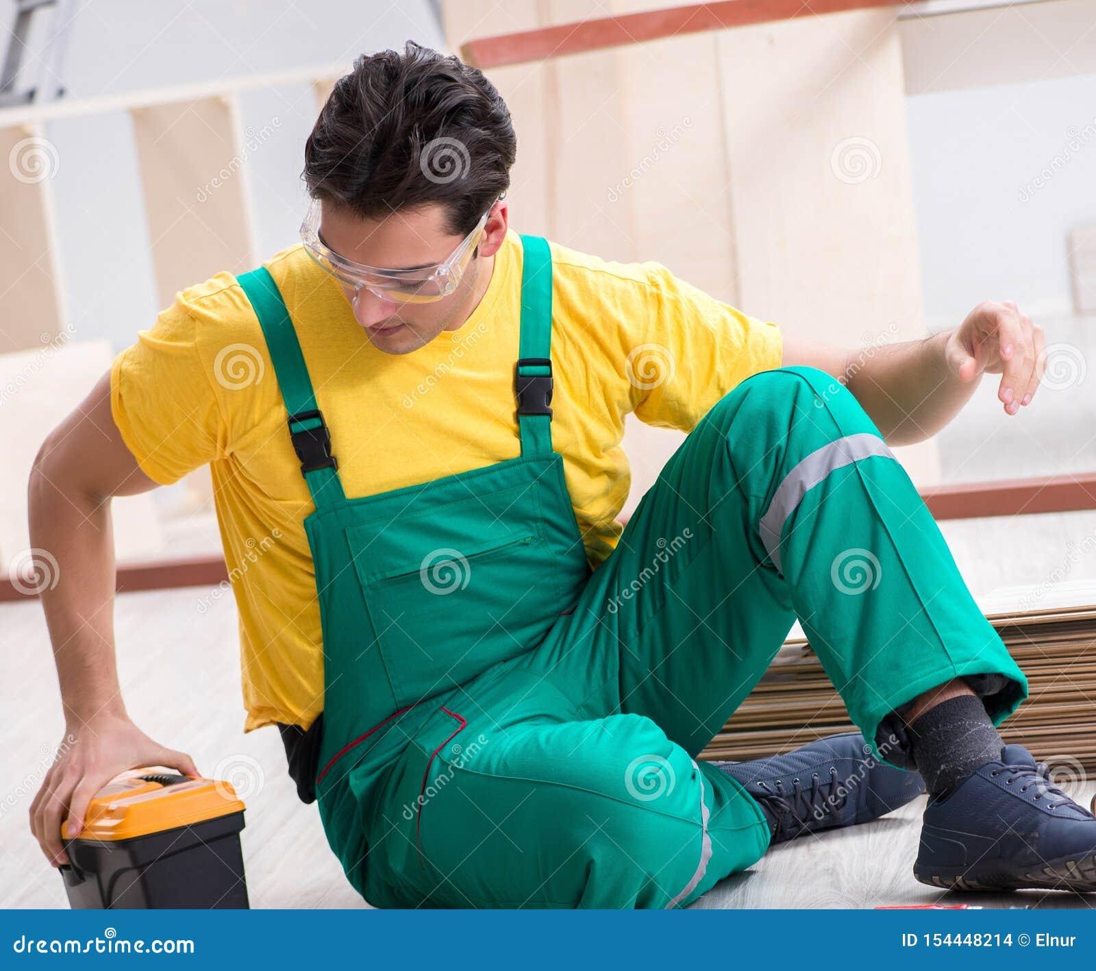 Ανάδοχος που εργάζεται στο φυλλόμορφο ξύλινο πάτωμα