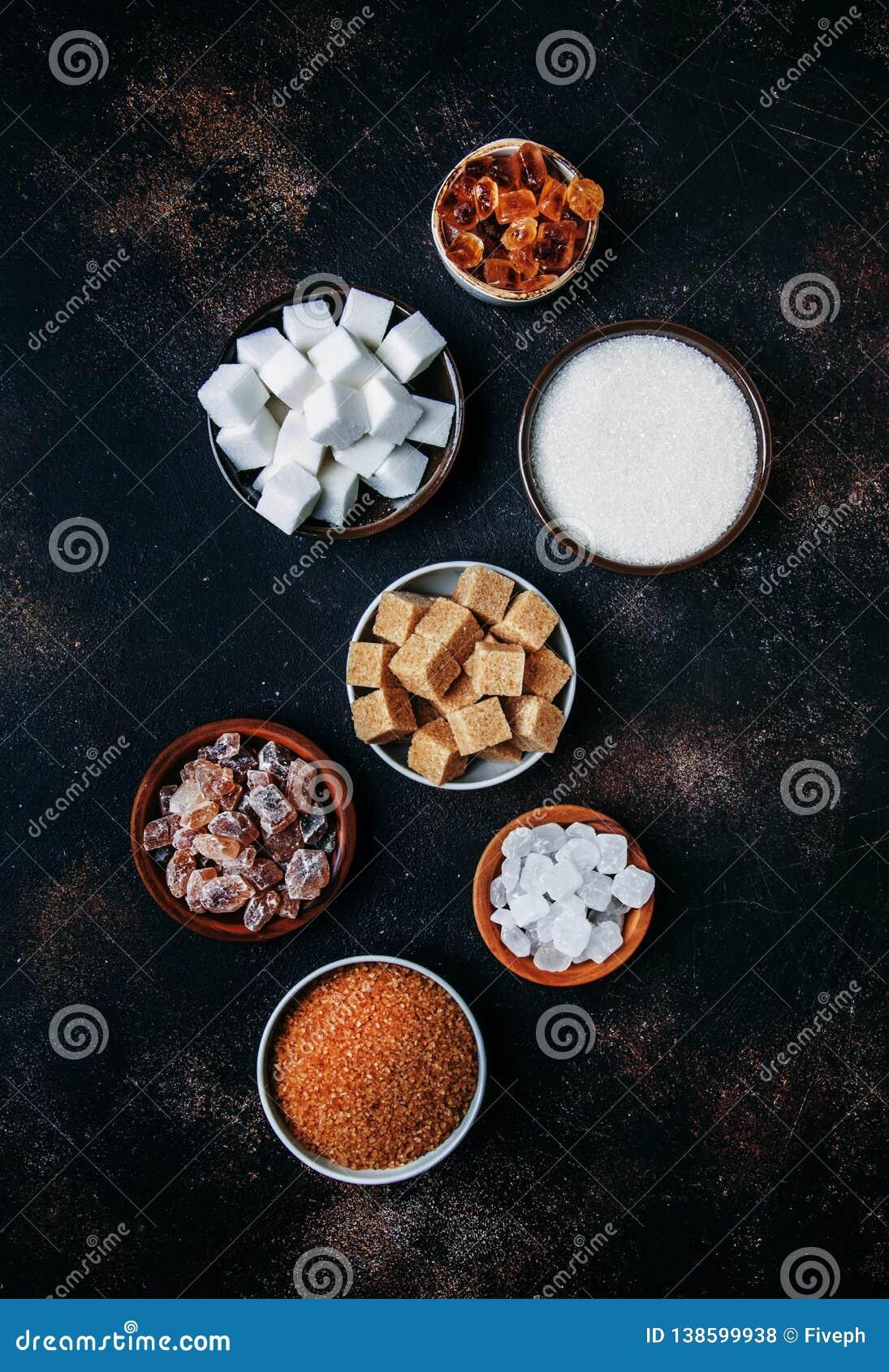 Ανάμεικτοι διαφορετικοί τύποι ζαχαρών στα κύπελλα σε έναν πίνακα σε ένα σκοτεινό υπόβαθρο, κάθετη εικόνα