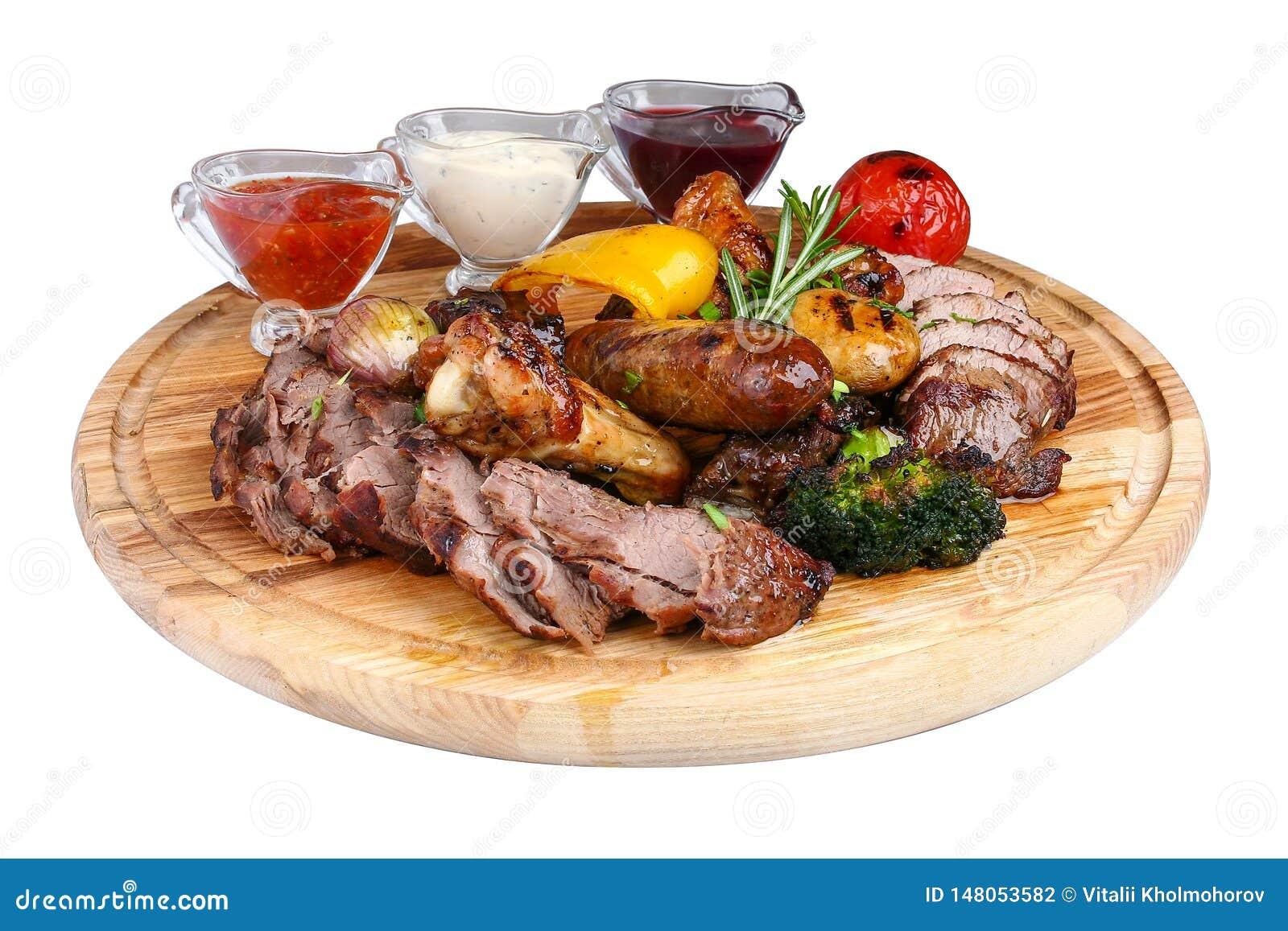 Ανάμεικτο ψημένο στη σχάρα κρέας με τα ψημένα λαχανικά σε έναν ξύλινο πίνακα