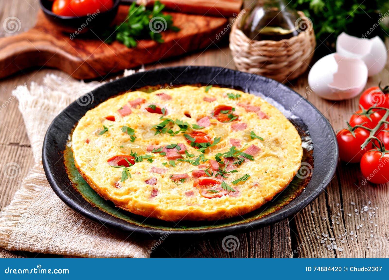 Ανακατωμένα αυγά με το ζαμπόν, την ντομάτα και το μαϊντανό