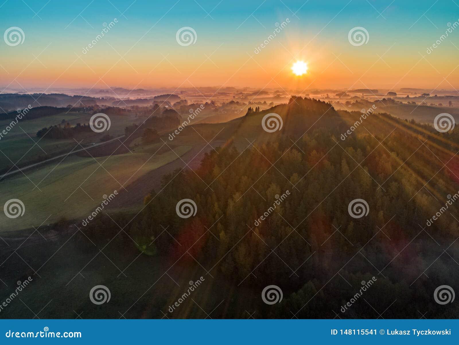 Ανατολή πέρα από ένα βουνό και ένα δάσος - εναέρια φωτογραφία