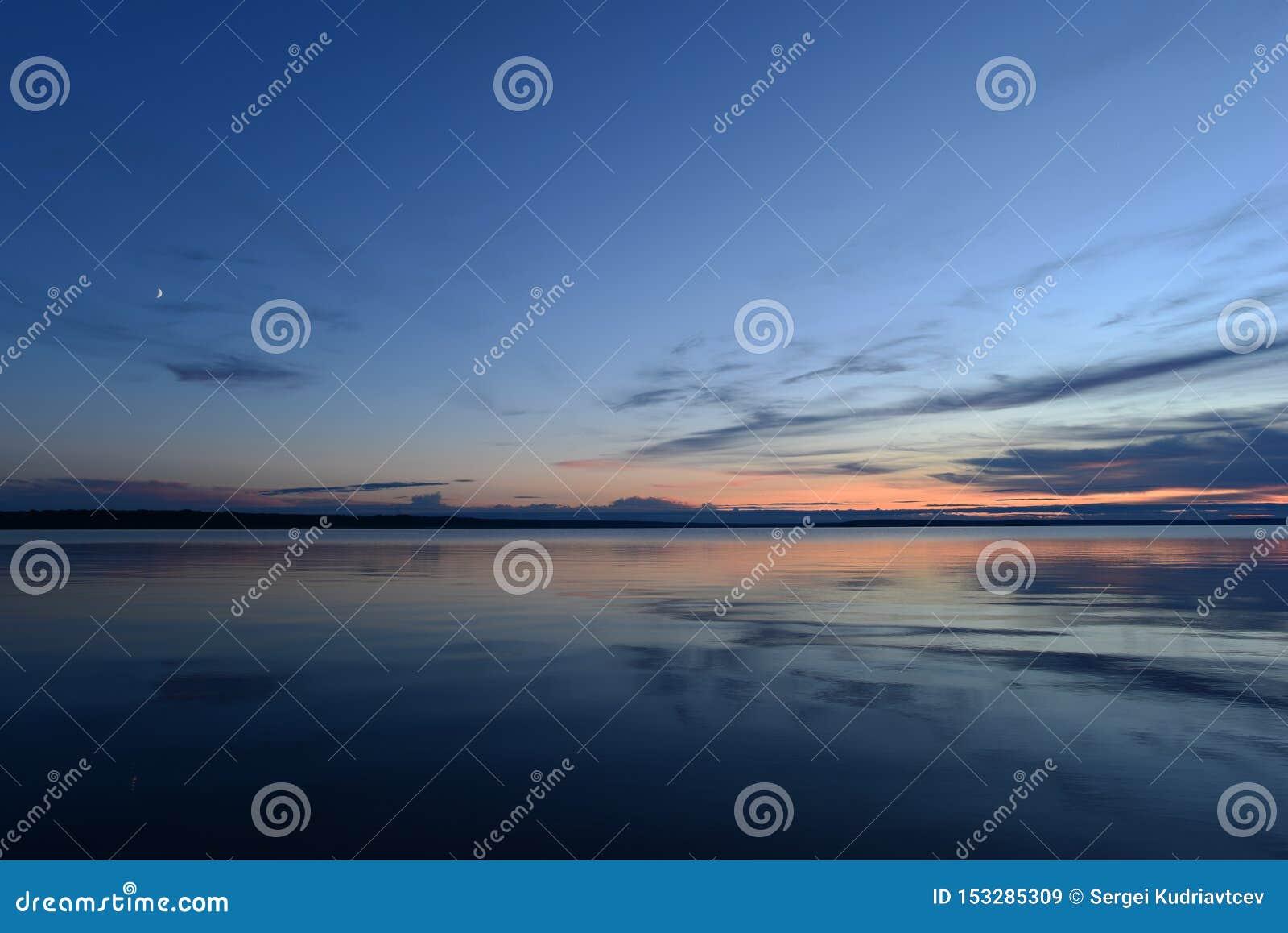 Ανατολή του φεγγαριού στο φως λυκόφατος στο μπλε ουρανό στο ηλιοβασίλεμα πέρα από το ήρεμο νερό καθρεφτών της λίμνης