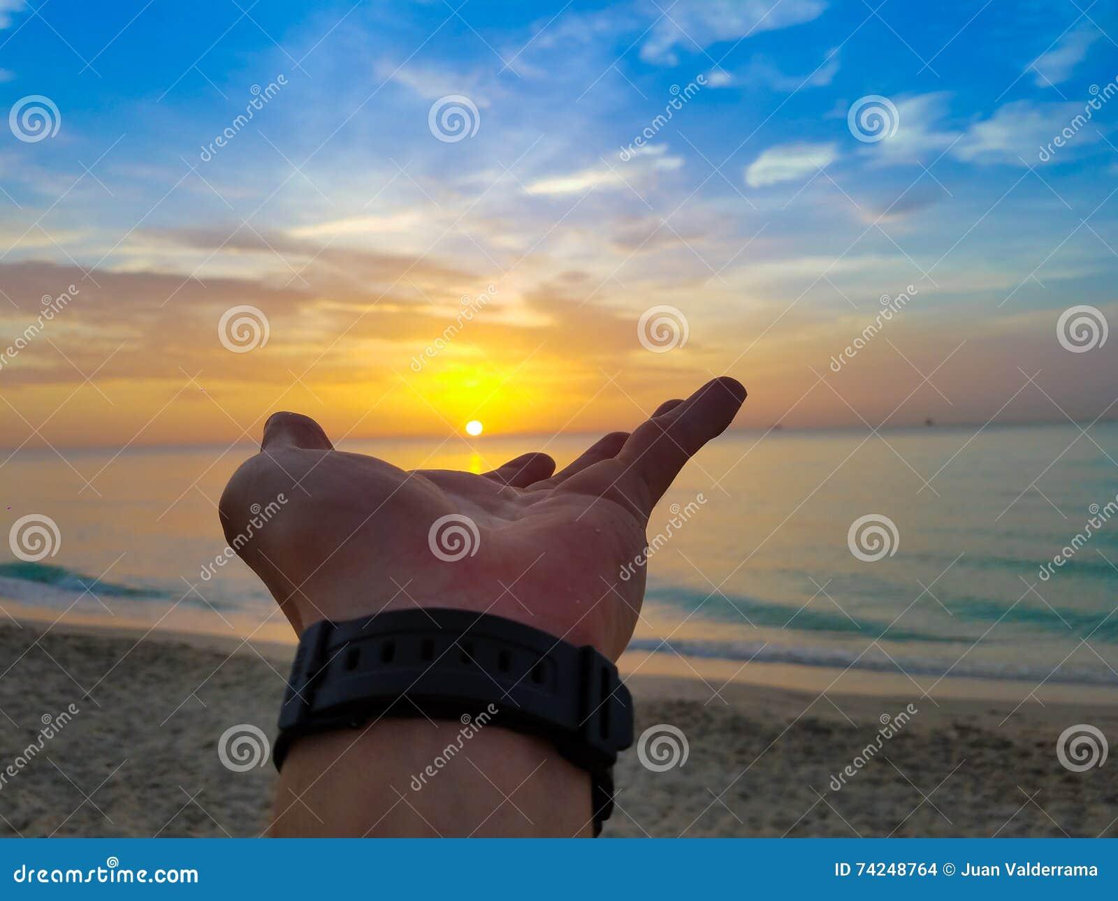 Ανατολή παραλιών με ένα χέρι του Θεού στον ήλιο