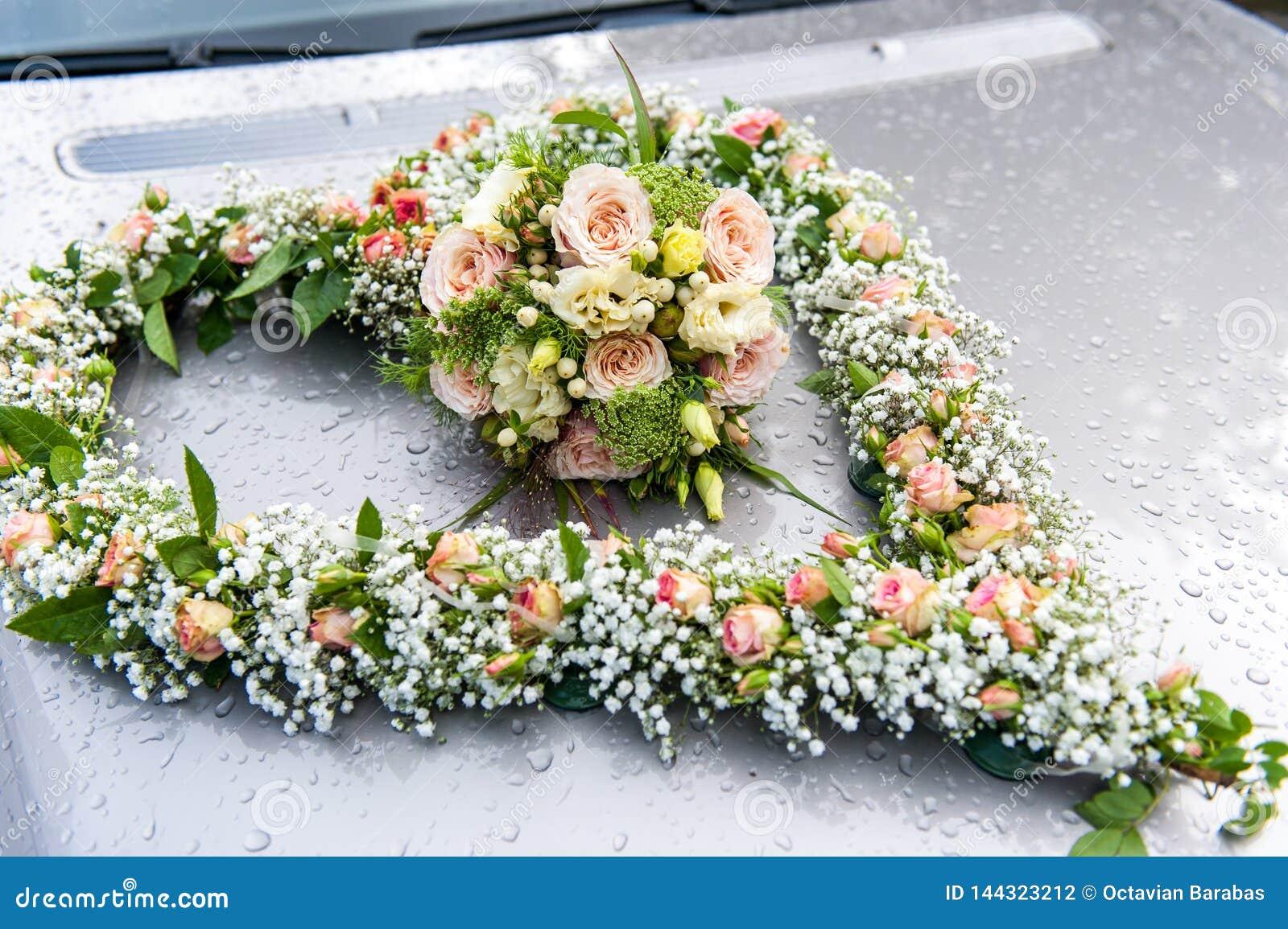 Ανθοδέσμη γαμήλιων λουλουδιών στη μορφή δαπέδων τζακιού στο καπό αυτοκινήτων