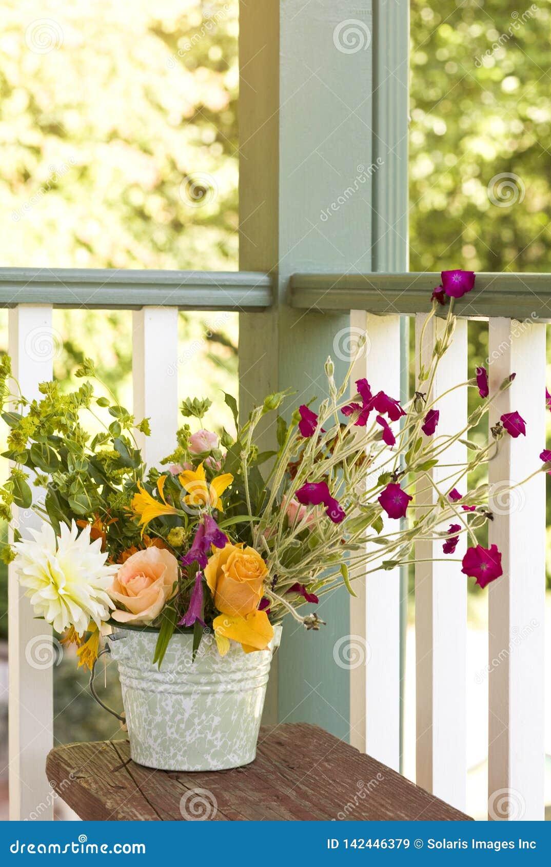 Ανθοδέσμη λουλουδιών στον κάδο κάδων στο μπροστινό μέρος Ντεκόρ θερινών σπιτιών απλού, ύφους χωρών