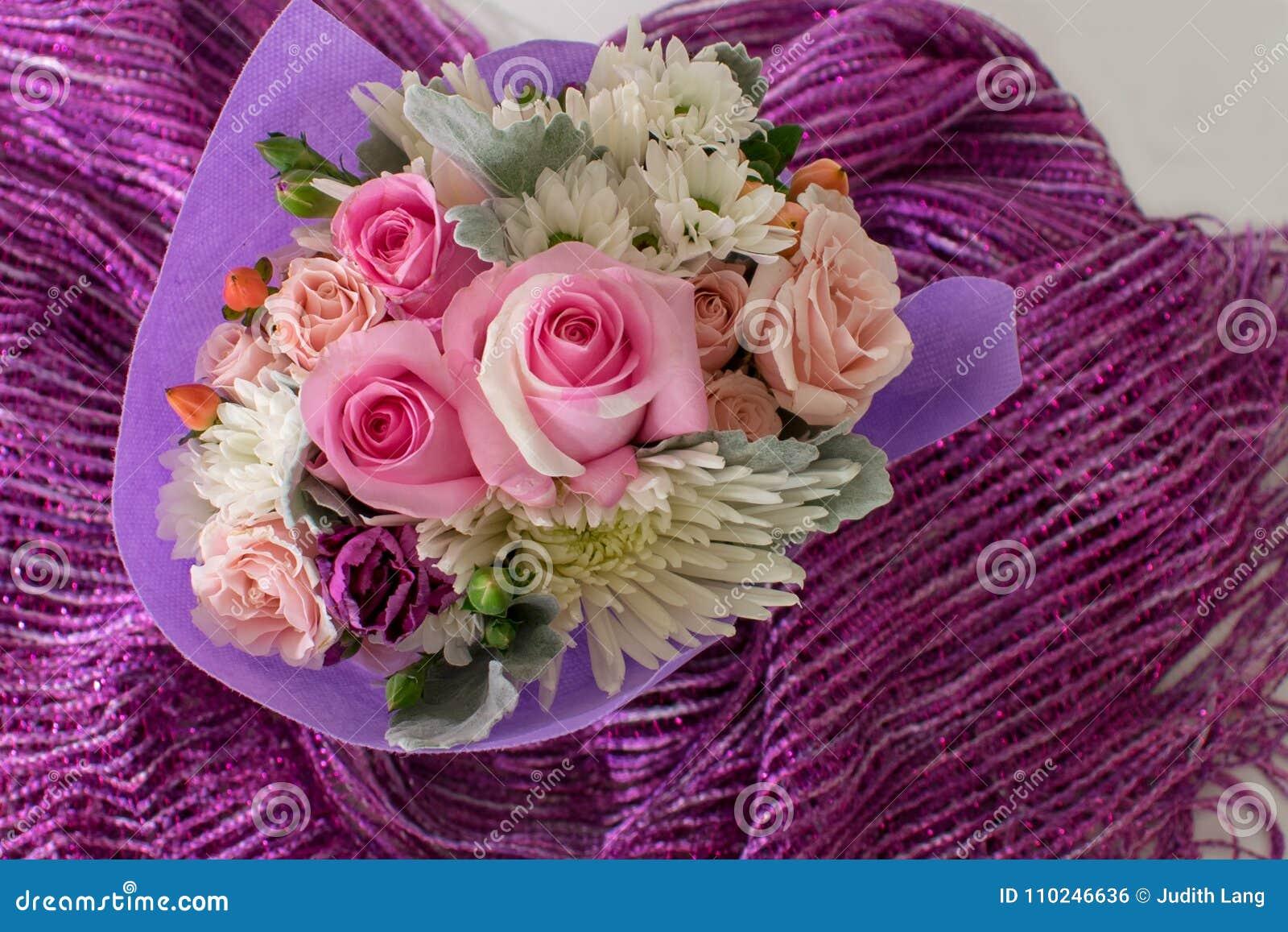 Ανθοδέσμη των μικρών τριαντάφυλλων και άλλων μικτών λουλουδιών στο πορφυρό ύφασμα