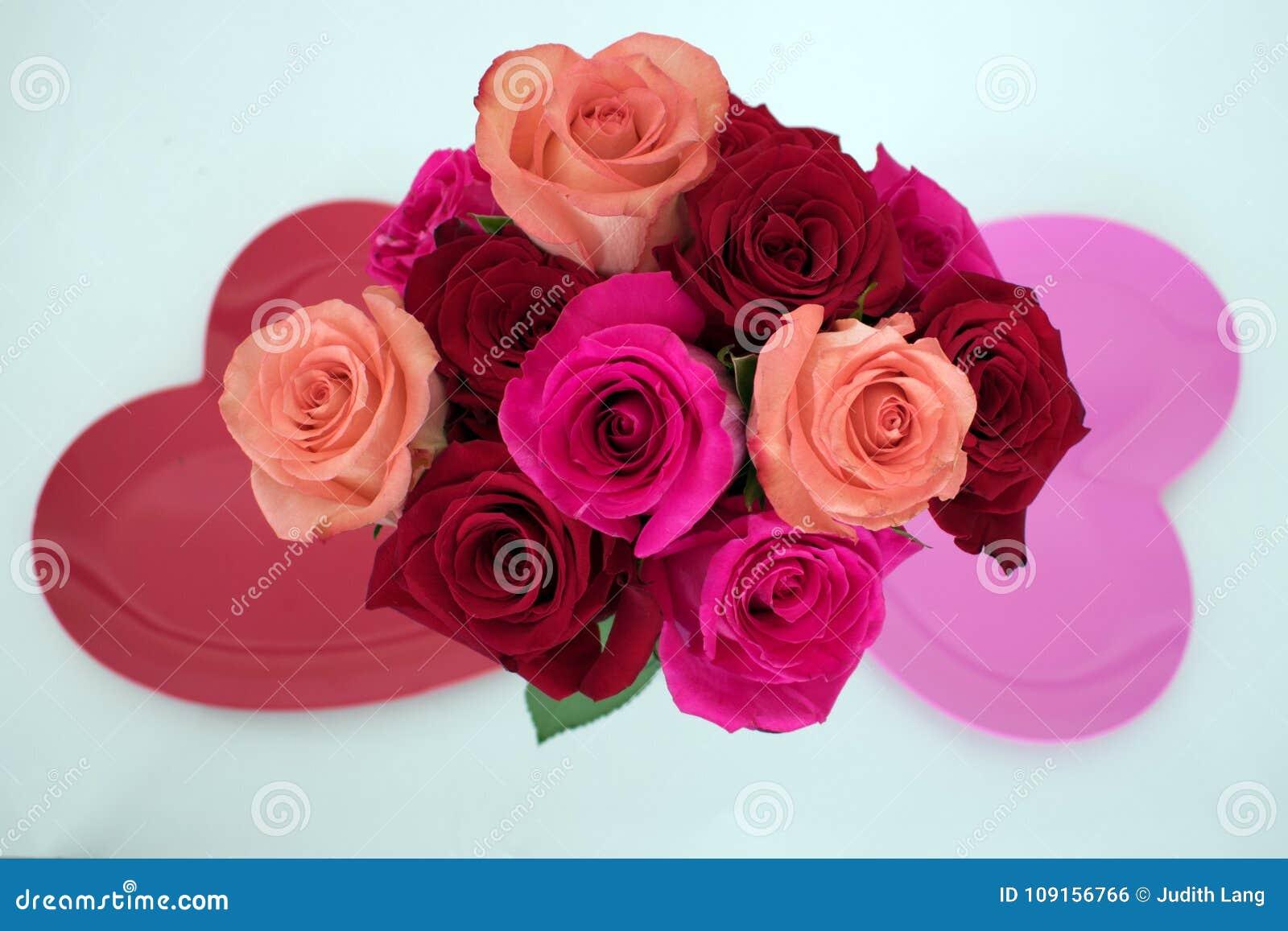 Ανθοδέσμη των τριαντάφυλλων μεταξύ δύο διαμορφωμένων καρδιά πιάτων