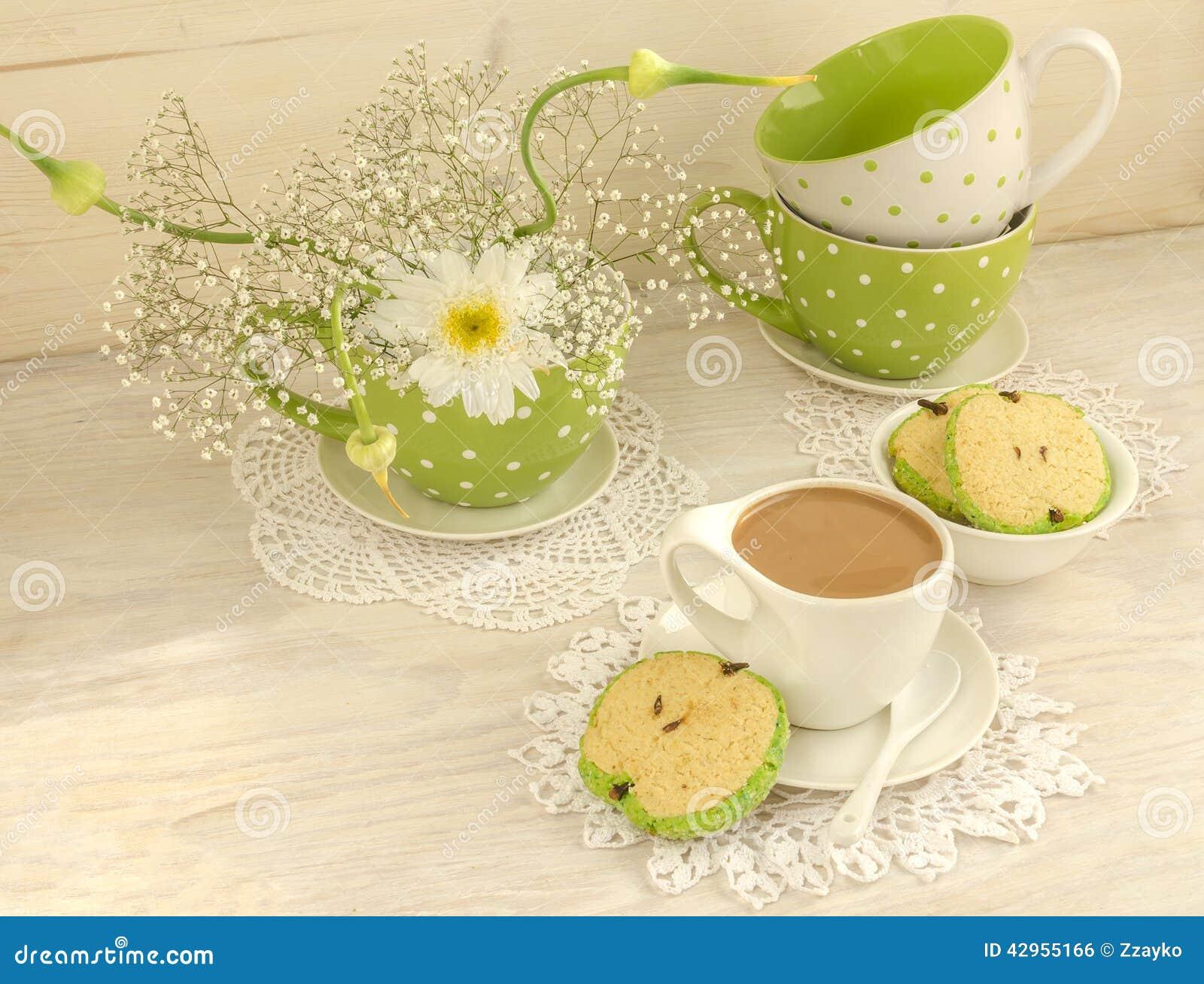 Ανθοδέσμη των άσπρων λουλουδιών, του κακάου φλυτζανιών με το γάλα και των με σχήμα μήλου μπισκότων