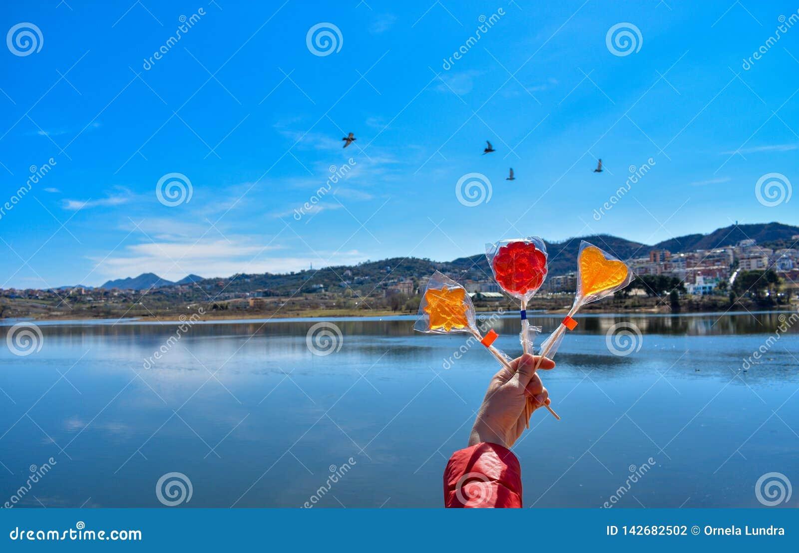 Ανθρώπινο χέρι που κρατά τα ζωηρόχρωμα lollipops ενάντια στην τεχνητή λίμνη