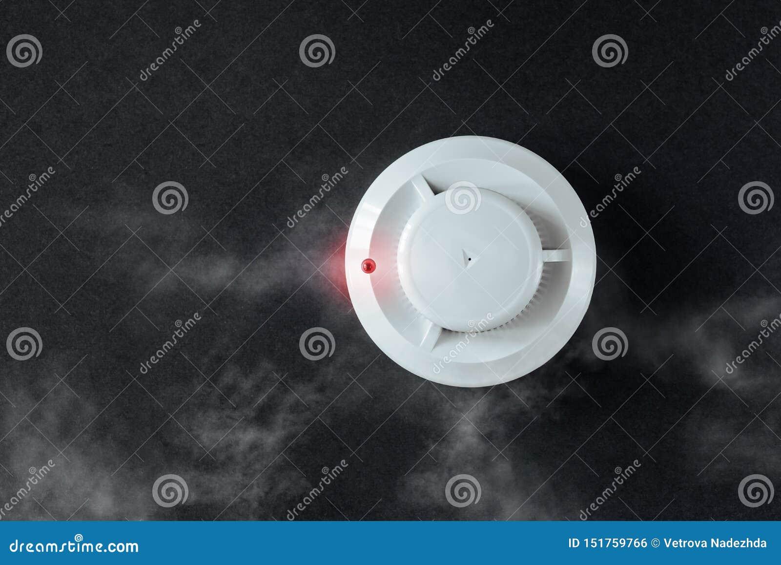 Ανιχνευτής καπνού και ανιχνευτής πυρκαγιάς σε ένα μαύρο υπόβαθρο Το επίπεδο συναγερμών πυρκαγιάς βρέθηκε